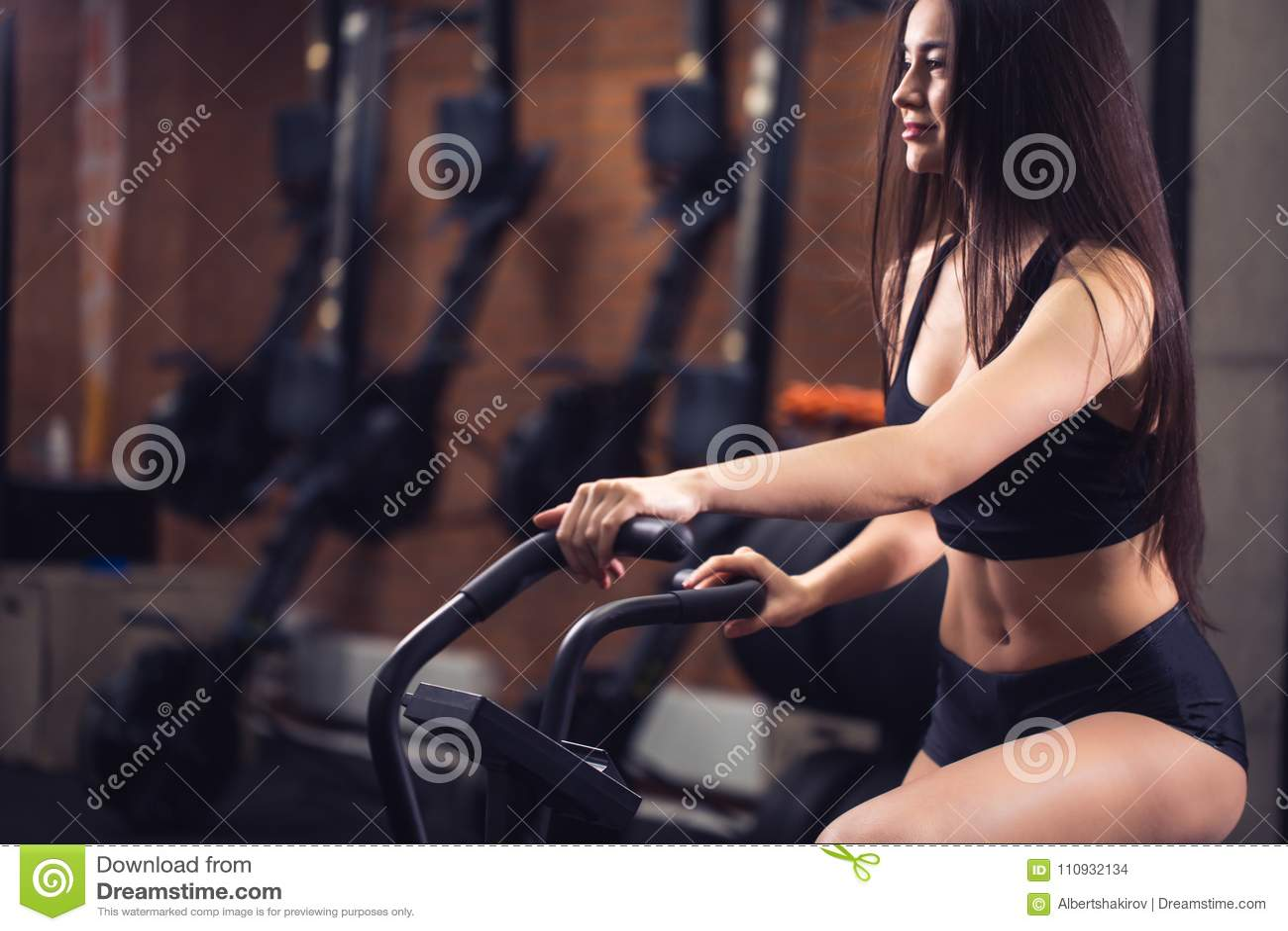 Kobieta jedzie ćwiczenie rower w gym dysponowana dziewczyna robi cardio szkoleniu na bicyklu
