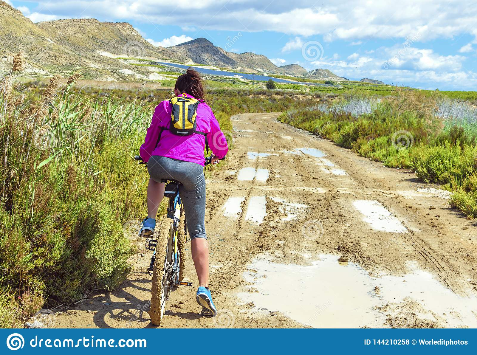 Kobieta jedzie rower górskiego błotnistą ścieżką brud