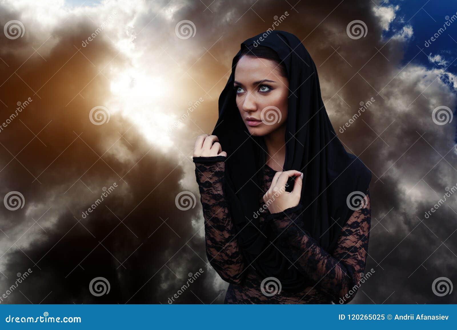 Kobieta jest profeta czarnoksiężnikiem i kaznodzieją w czarnej mistycznej pelerynie z kapiszonem przeciw dramatycznemu tłu
