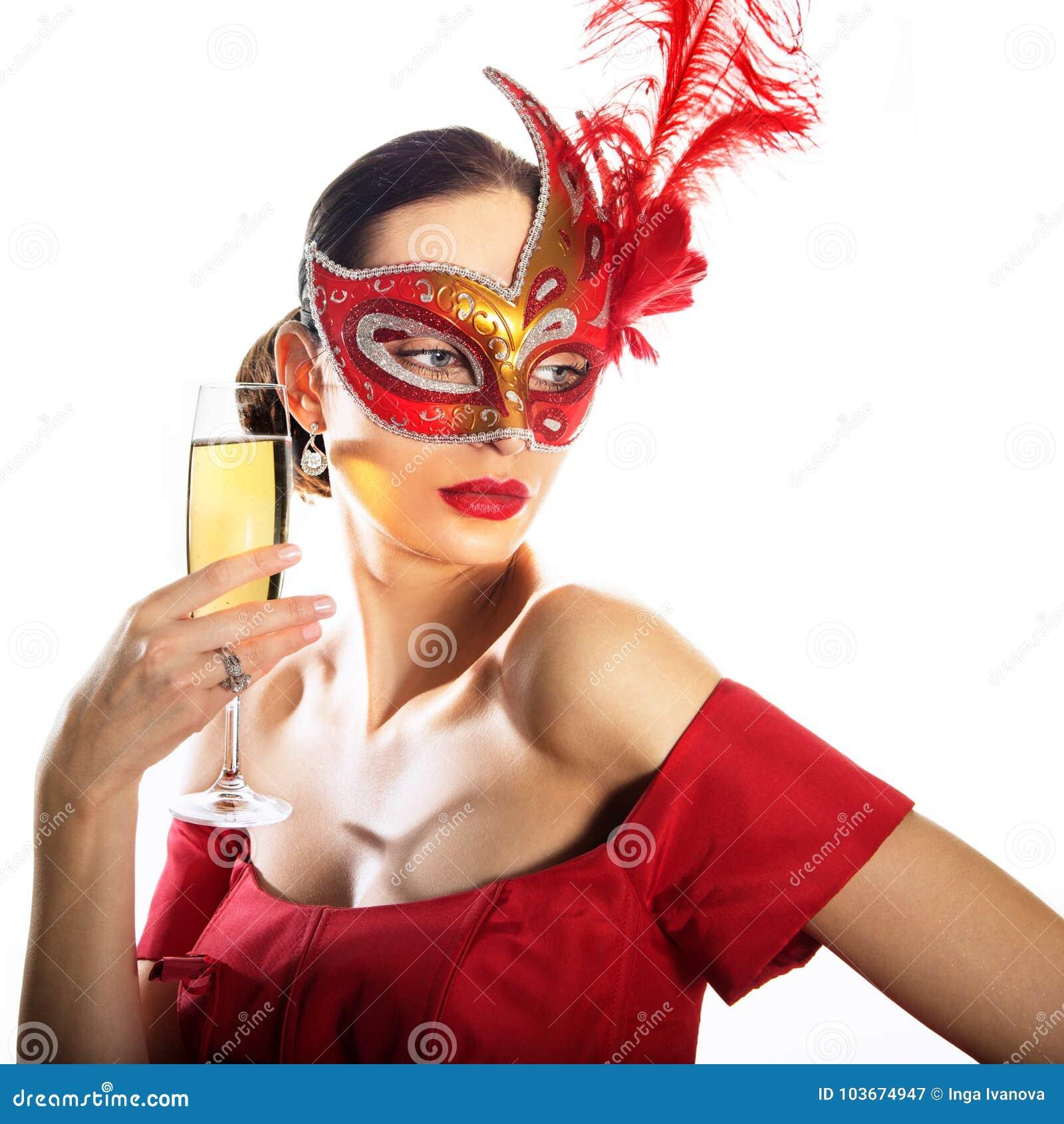Kobieta jest ubranym karnawał maskę z szkłem szampan