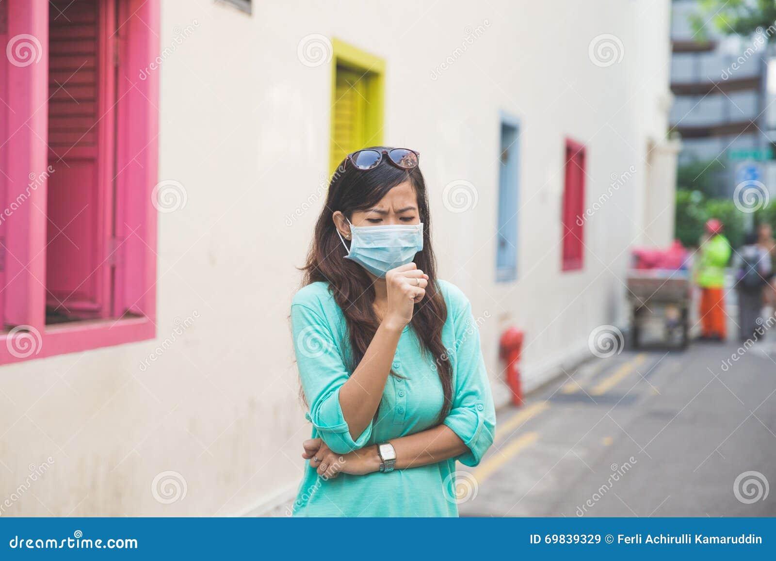Kobieta jest ubranym medyczną twarzy maskę w mieście