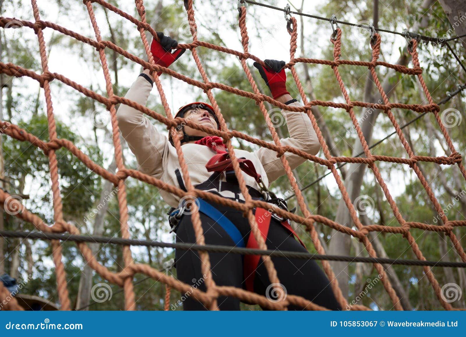 Kobieta jest ubranym zbawczego hełma pięcie na linowym ogrodzeniu