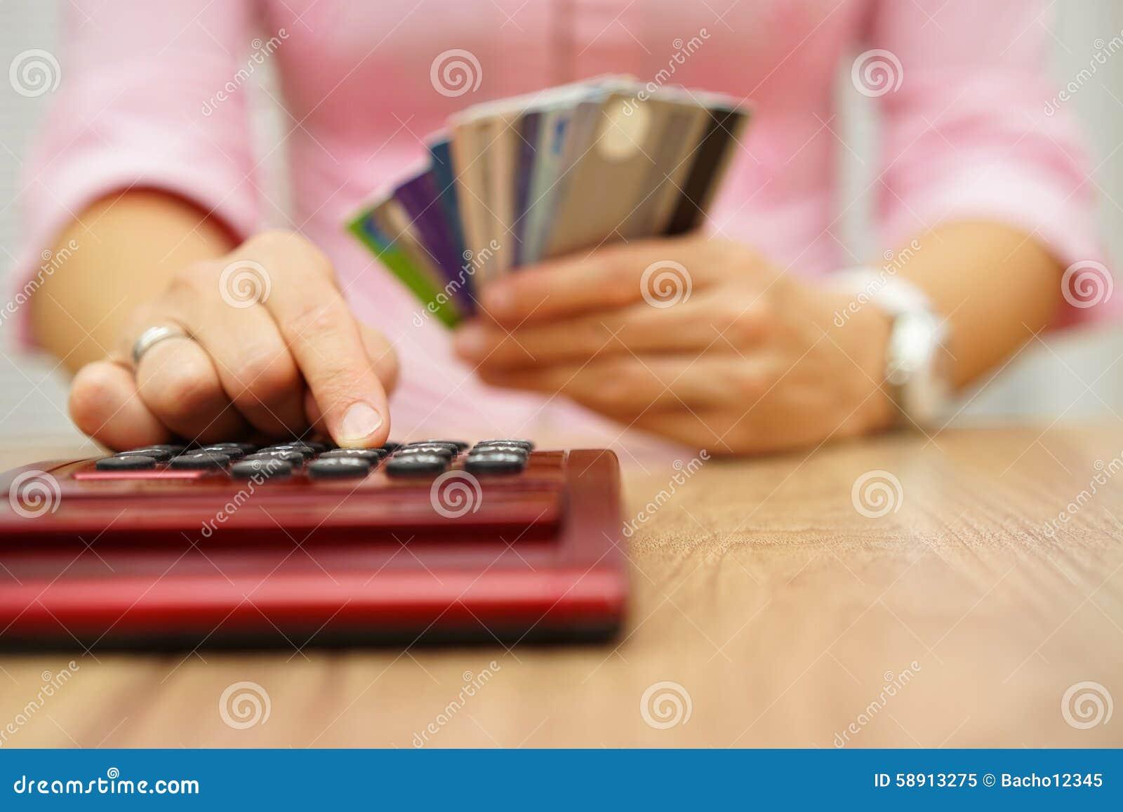 Kobieta kalkuluje ile kosztu lub wydatki z kredytowymi kartami