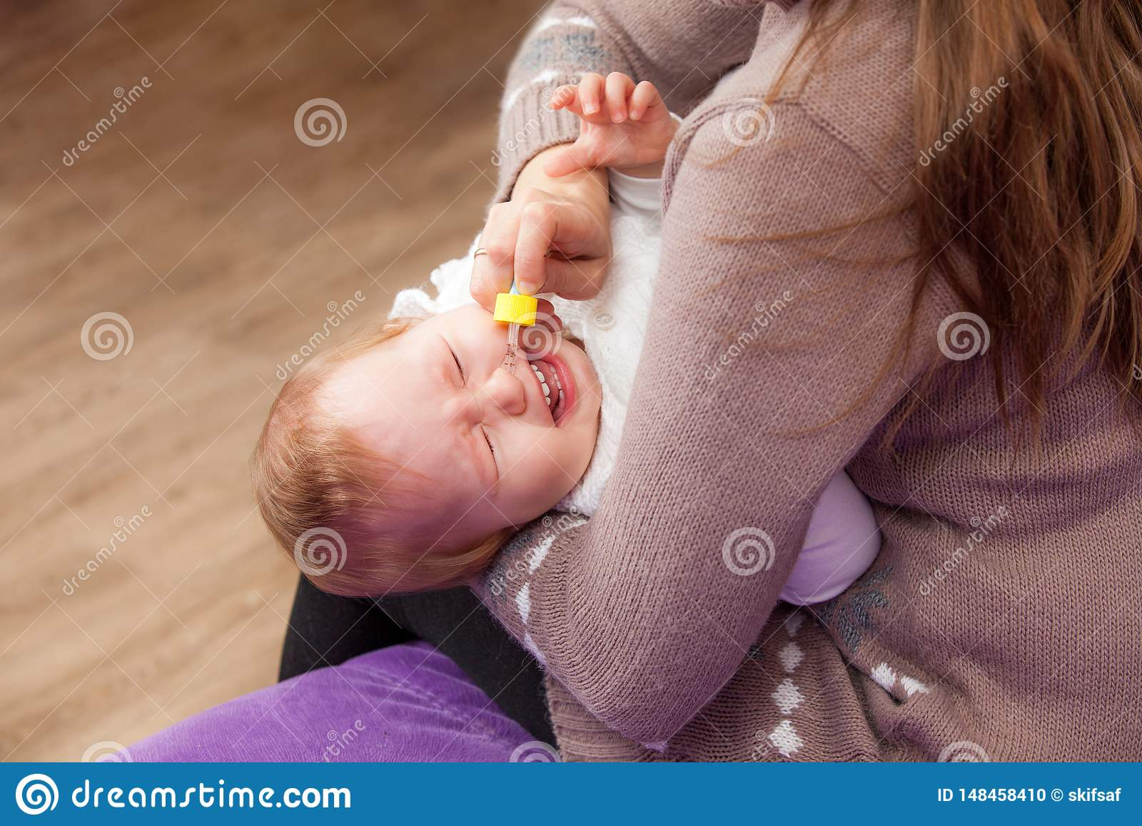 Kobieta kapie nosowe krople dziecko