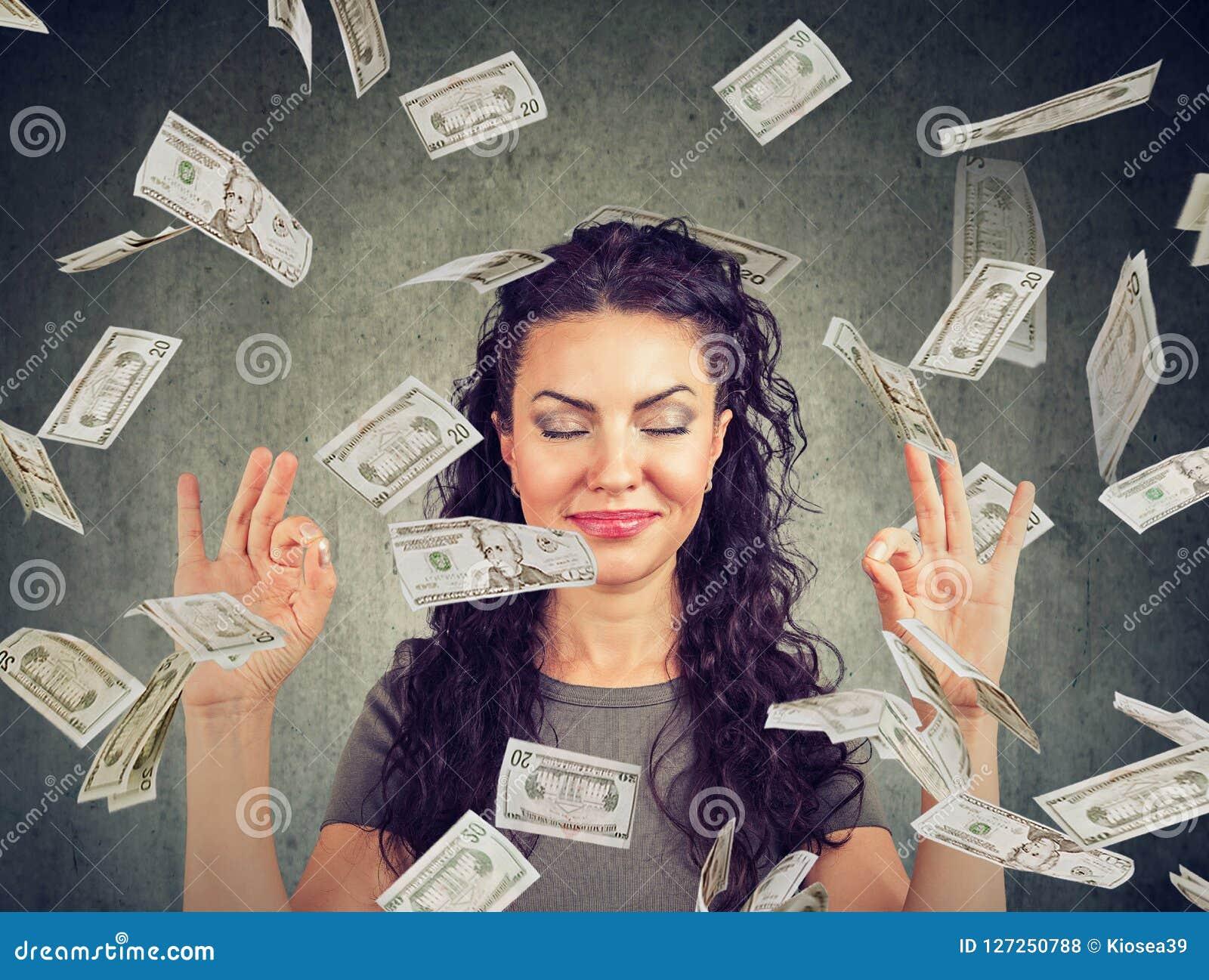 Kobieta medytuje pod pieniądze deszczem