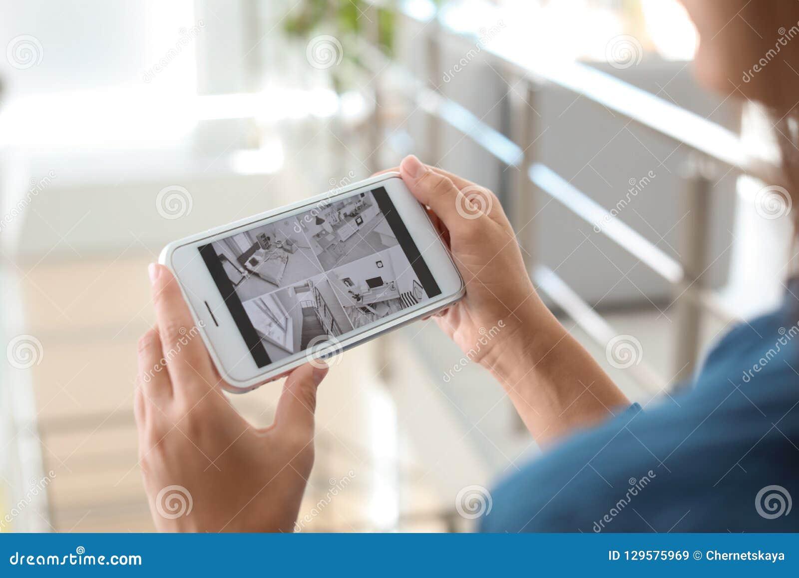 Kobieta monitoruje nowożytne cctv kamery na smartphone indoors