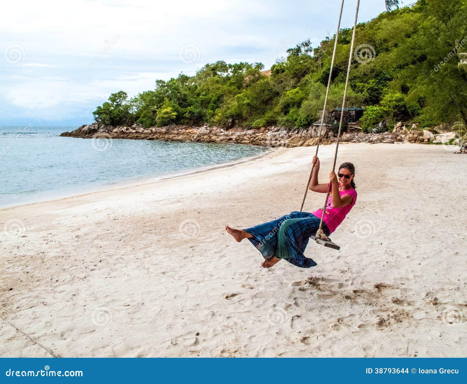 Kobieta na huśtawce przy tropikalną plażą