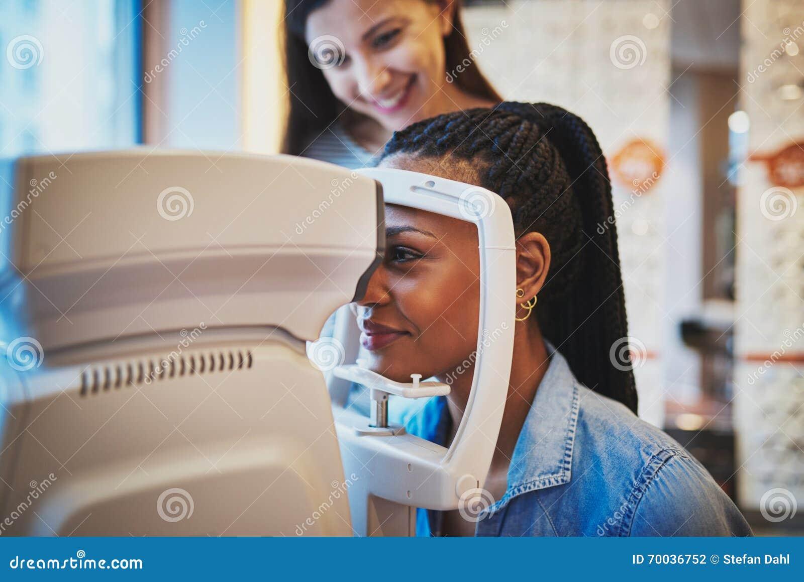 Kobieta naciska jej czoło okulistyczna maszyna