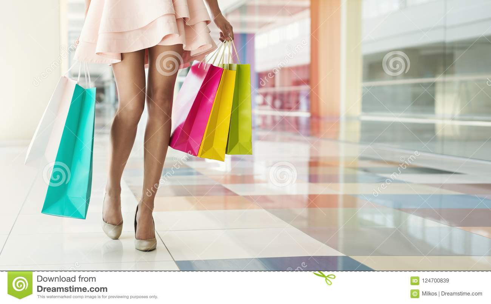 Kobieta niesie kolorowych torba na zakupy w centrum handlowym