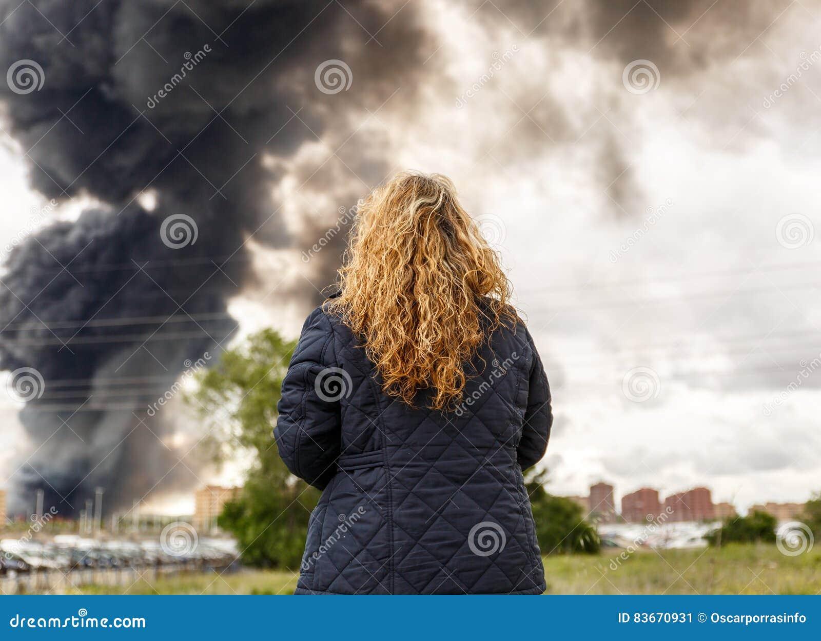 Kobieta obserwuje wielkiego dymnego przybycie od ogienia