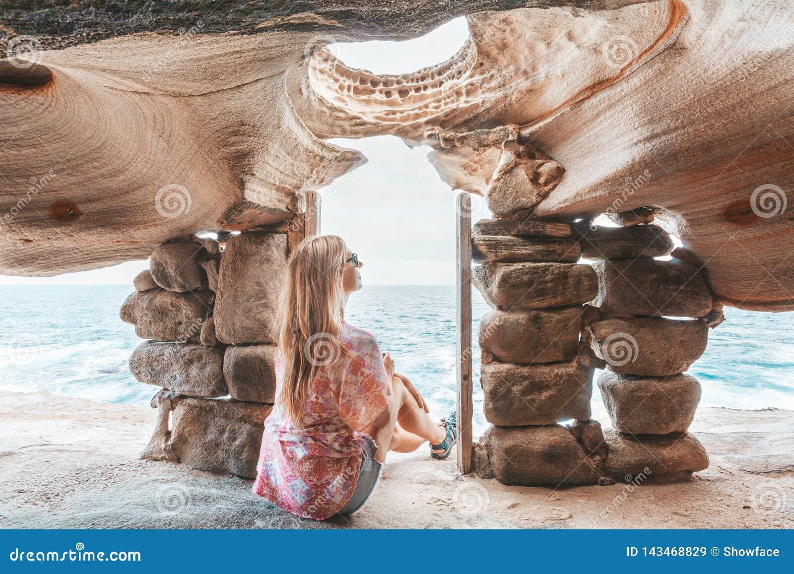 Kobieta ogląda ocean siedzi wśrodku faleza wierzchołka jamy