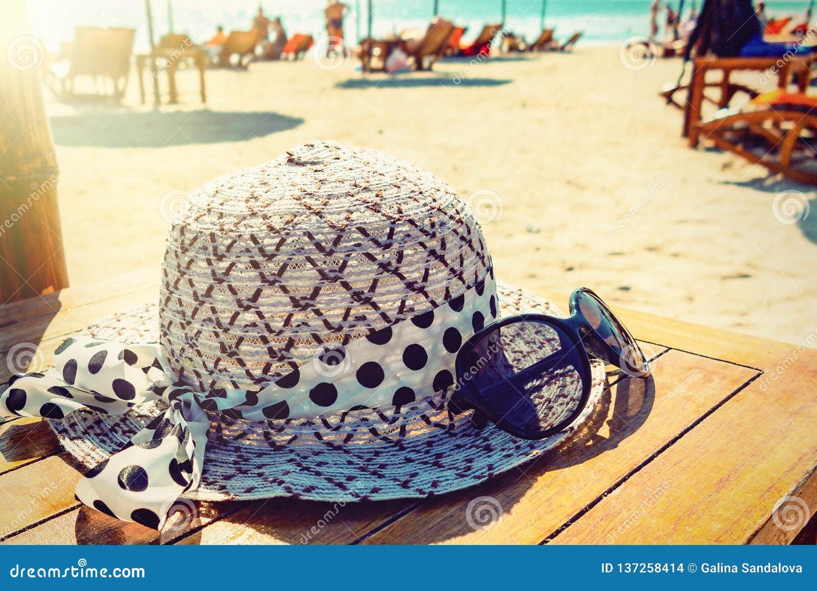 Kobieta okulary przeciwsłoneczni i kapelusz kłamamy na drewnianym stole na pogodnej piaskowatej plaży morzem