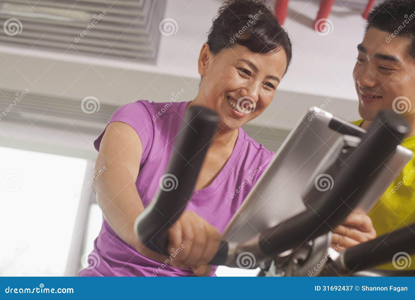 Kobieta ono uśmiecha się i ćwiczy na ćwiczenie rowerze z jej trenerem