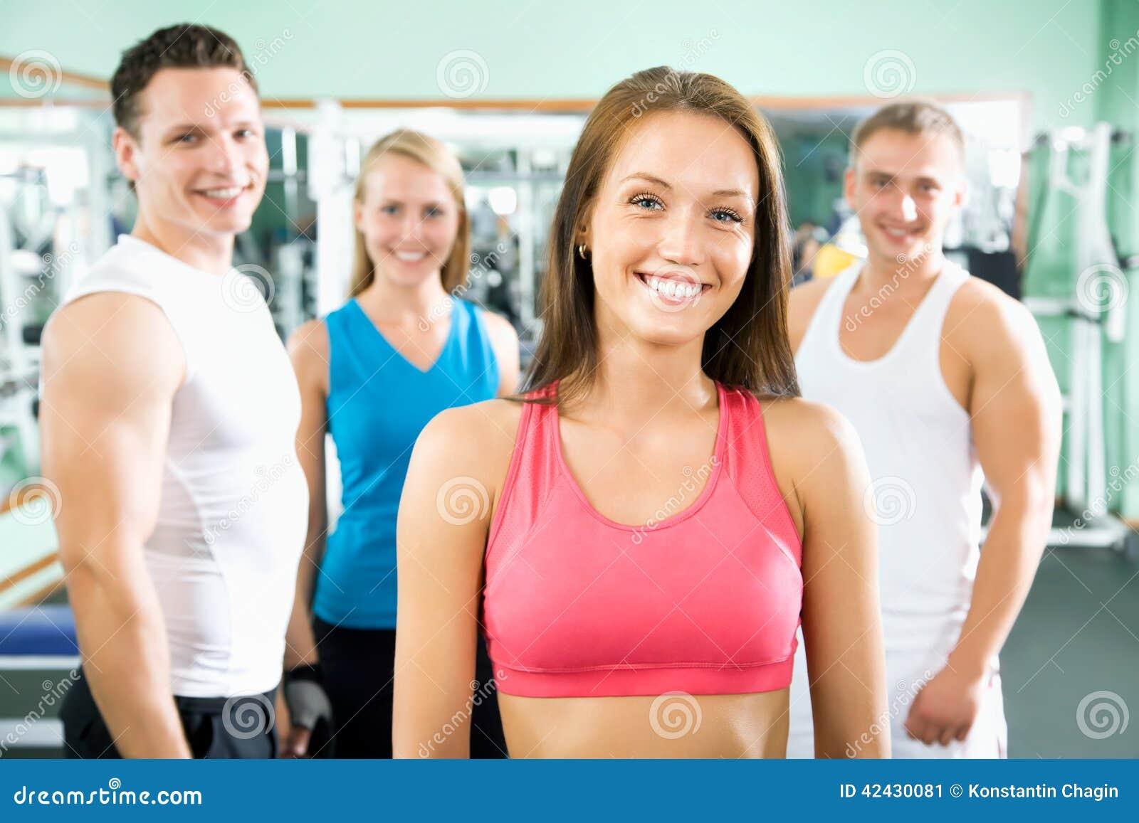 Kobieta ono uśmiecha się przed grupą gym ludzie