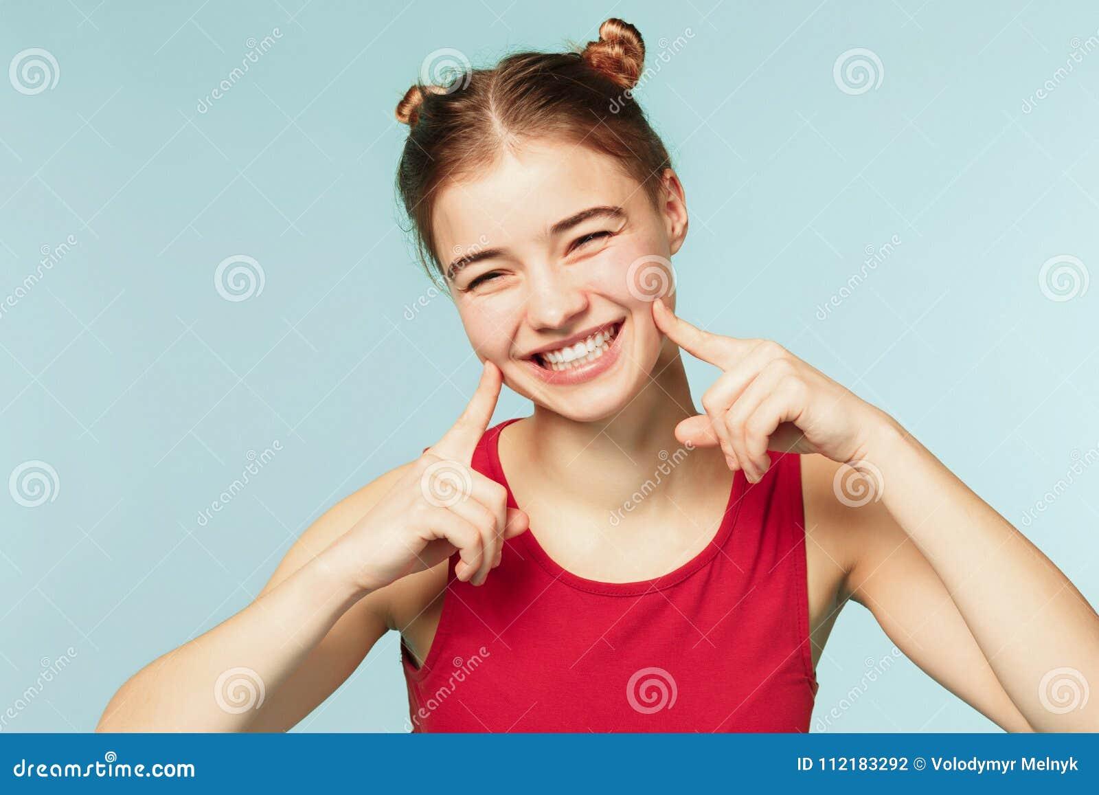 Kobieta ono uśmiecha się z perfect uśmiechem na błękitnym pracownianym tle