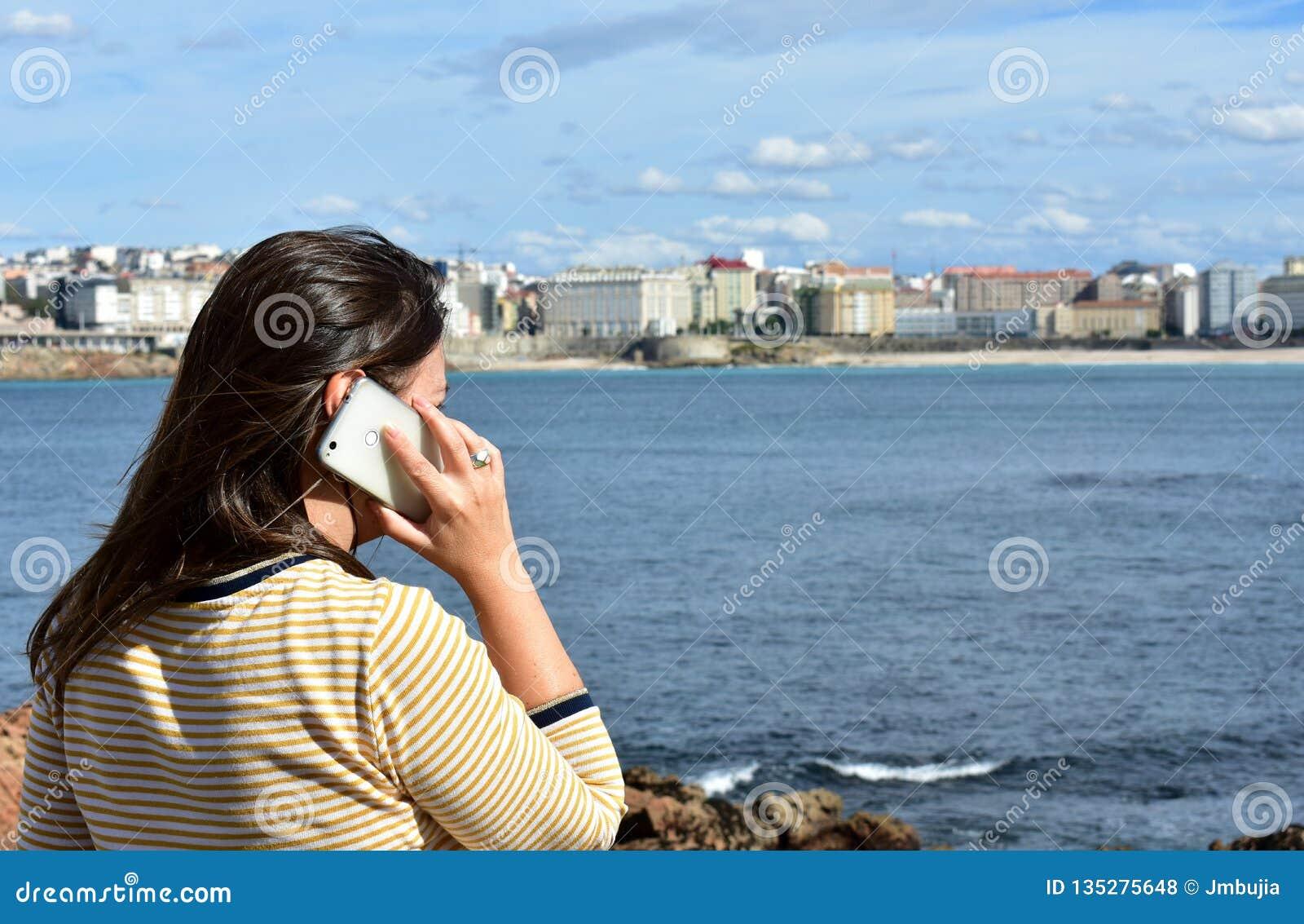 Kobieta opowiada na smartphone w zatoce Plaży, deptaka i miasta widok,