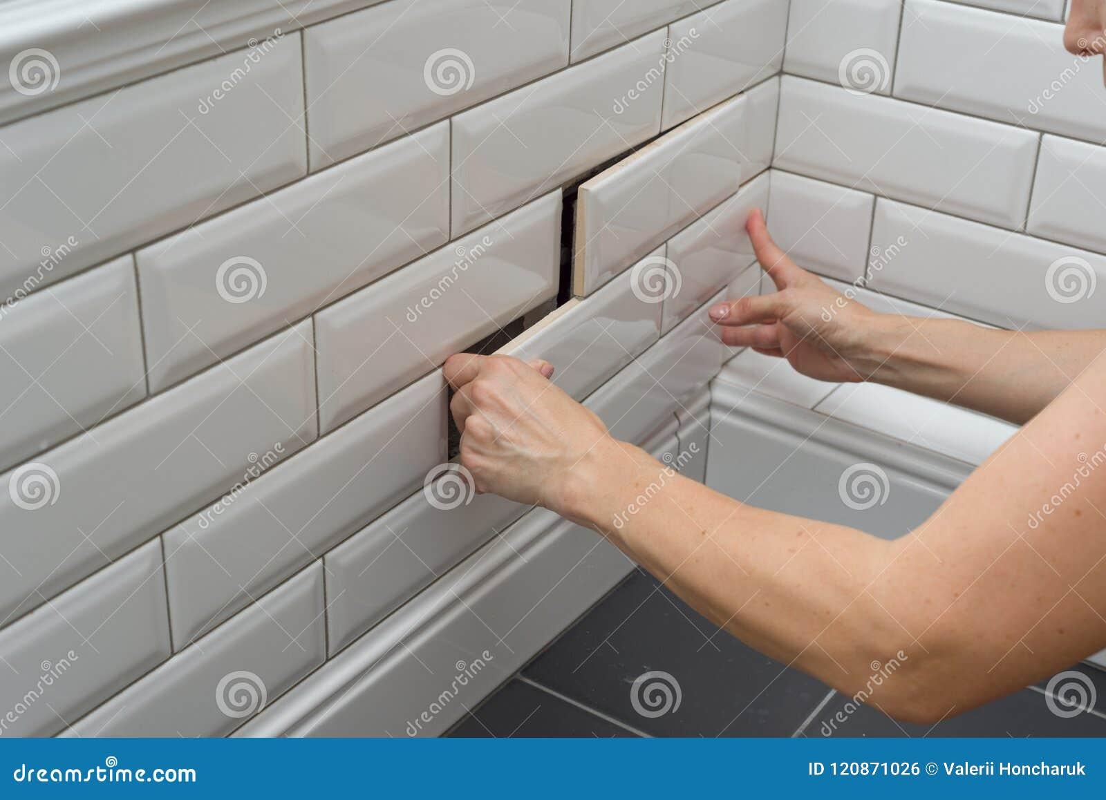 Kobieta otwiera, zamyka chowanego przeglądu sanitarnego ląg na ścianie płytka pod łazienką,