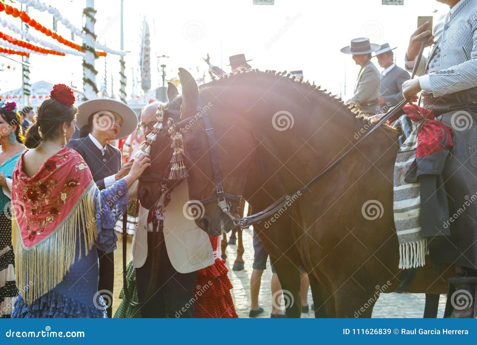 Kobieta pieszczotliwy koń i ubierający w tradycyjnych kostiumach przy Seville ` s Kwiecień jarmarkiem