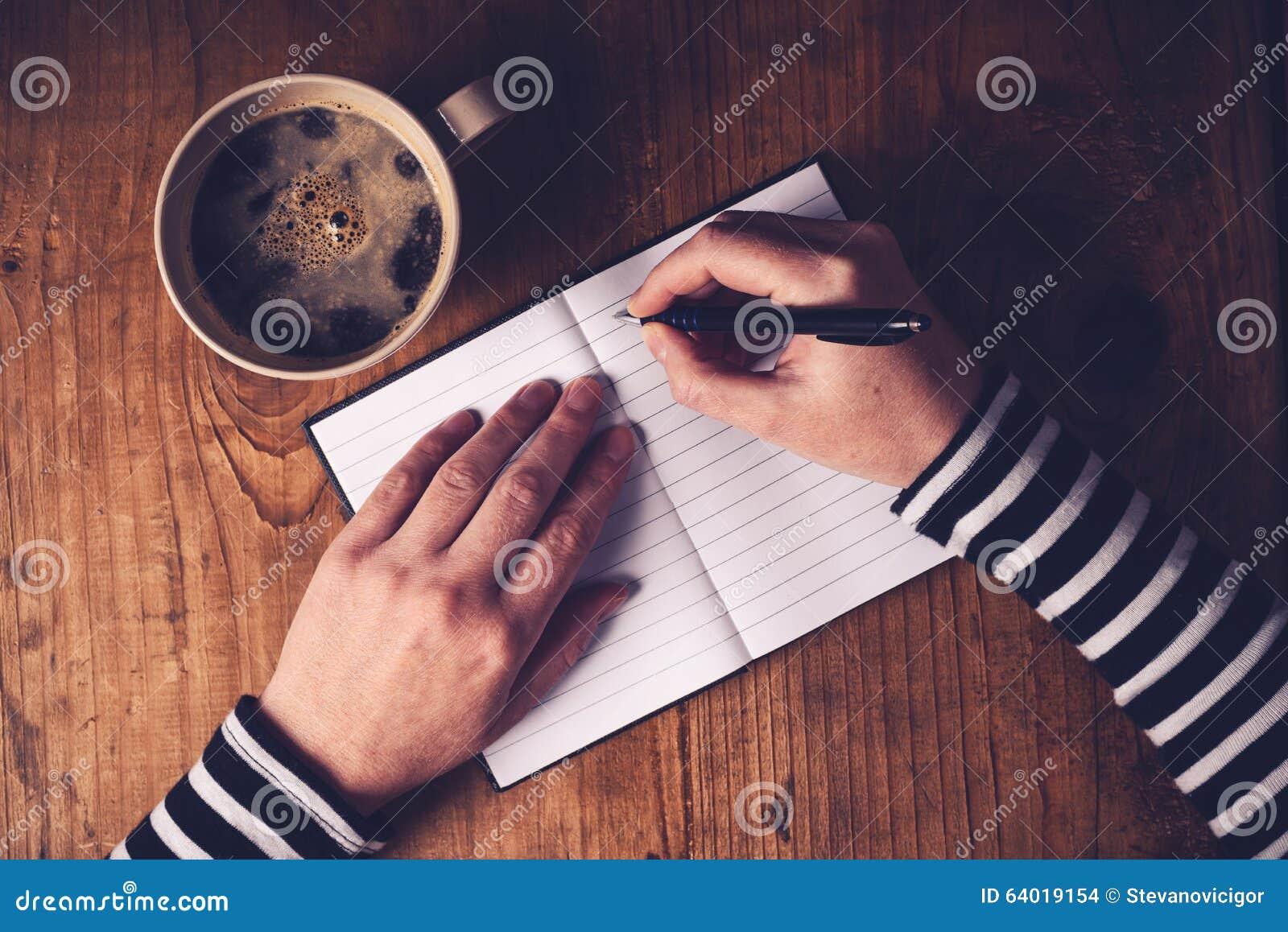 Kobieta pije kawę i pisze dzienniczek notatce