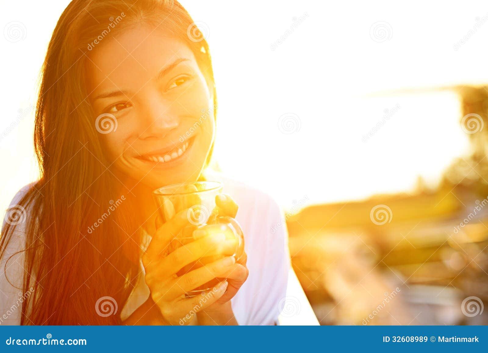 Kobieta pije kawę w świetle słonecznym