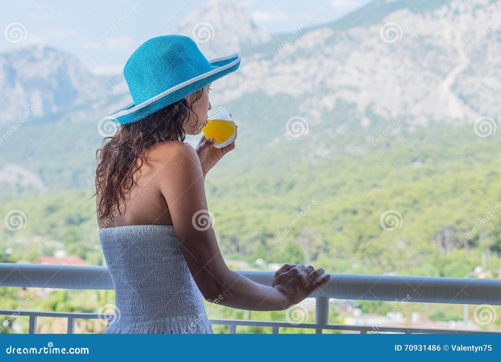 Kobieta pije sok pomarańczowego na hotelowym balkonie