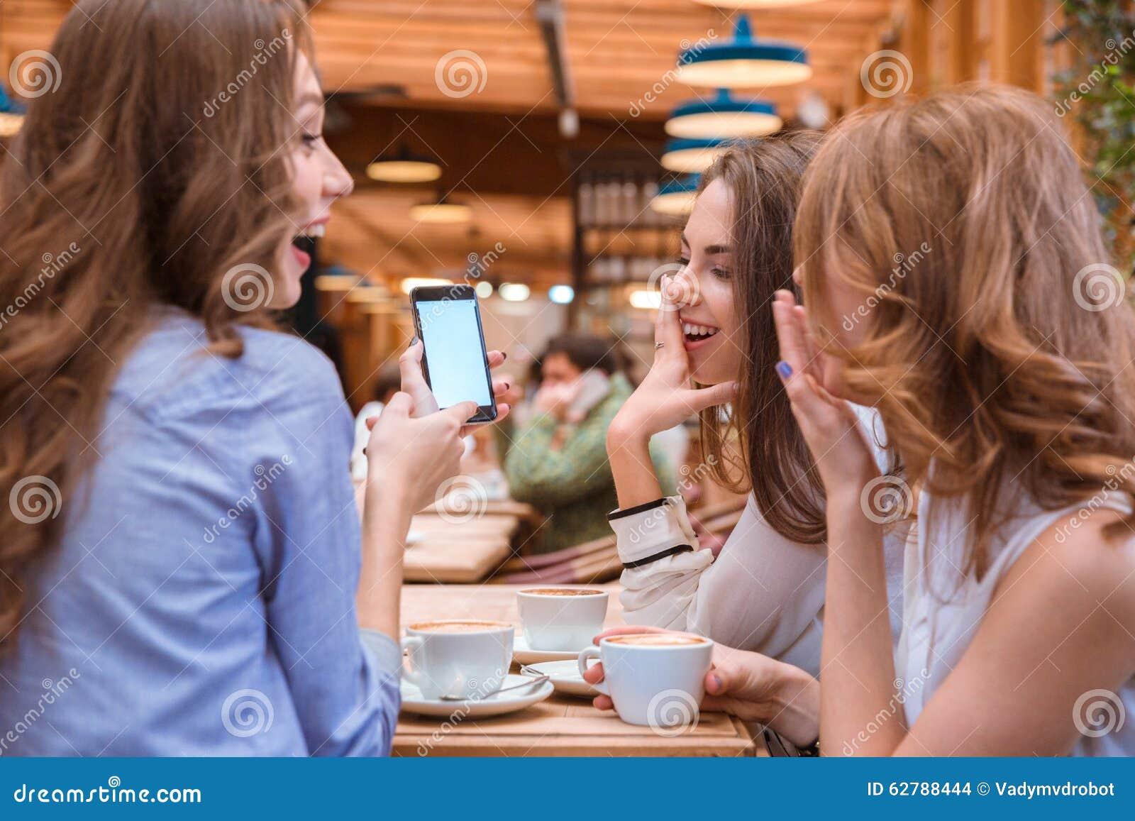 Kobieta pokazuje coś na smartphone ekranie jej dziewczyny