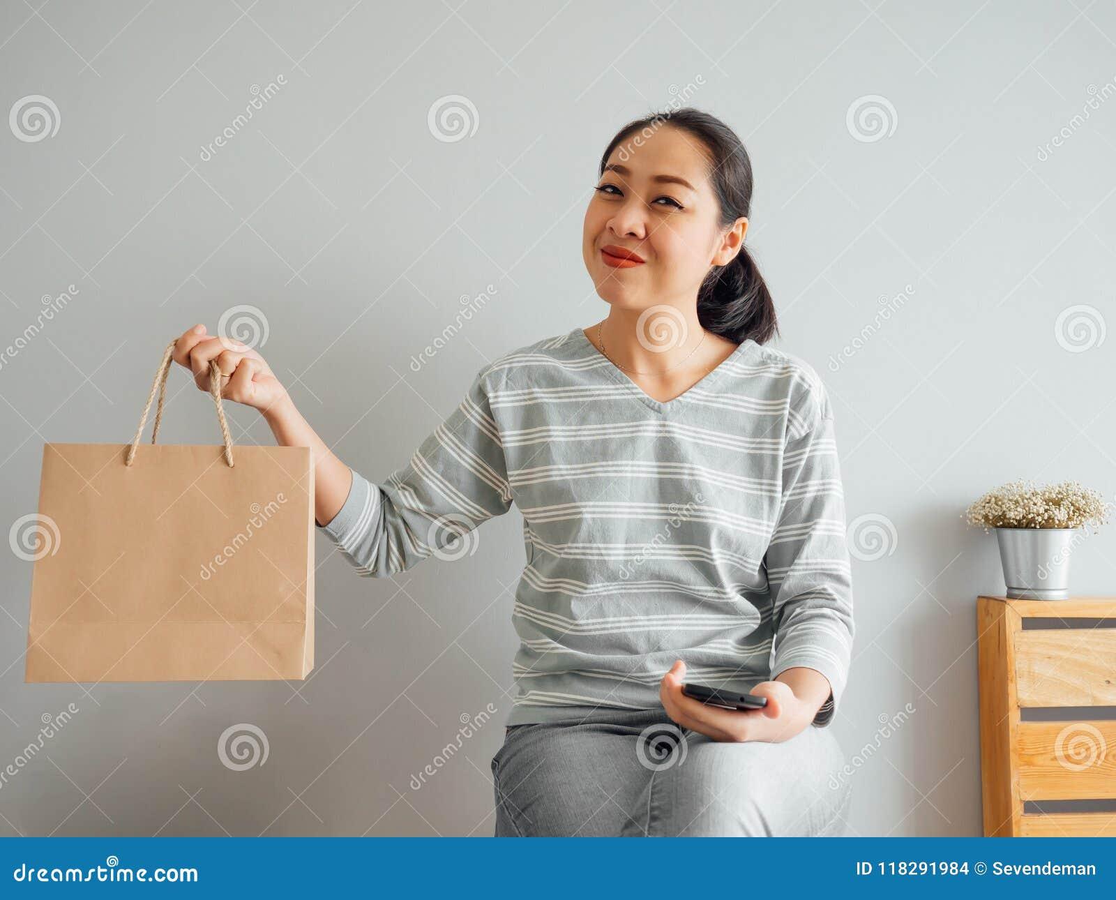 Kobieta pokazuje daleko pust? papierow? torb? produkt nabywa? online Poj?cie online zakupy