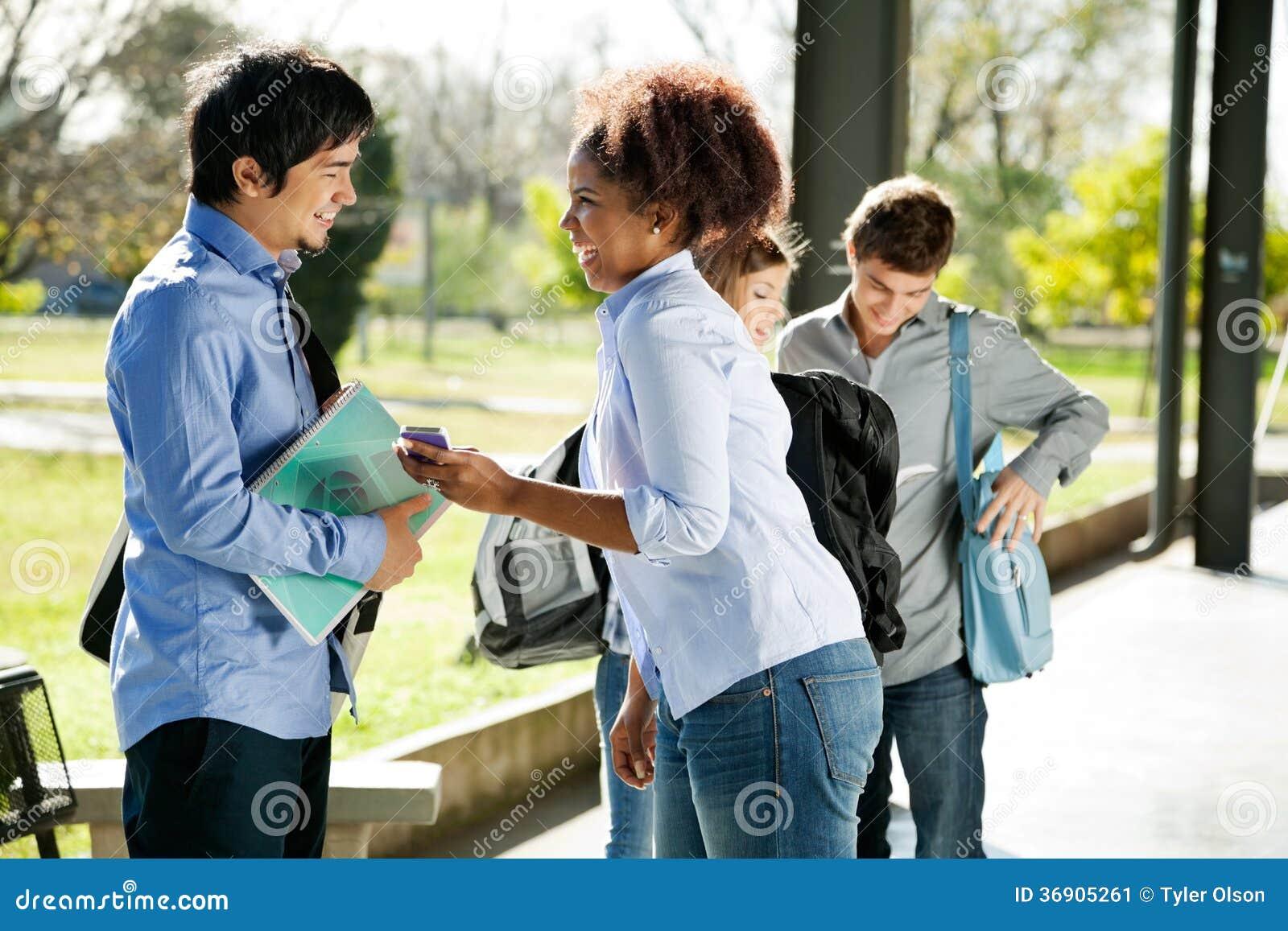 Kobieta Pokazuje telefon komórkowego przyjaciel W kampusie