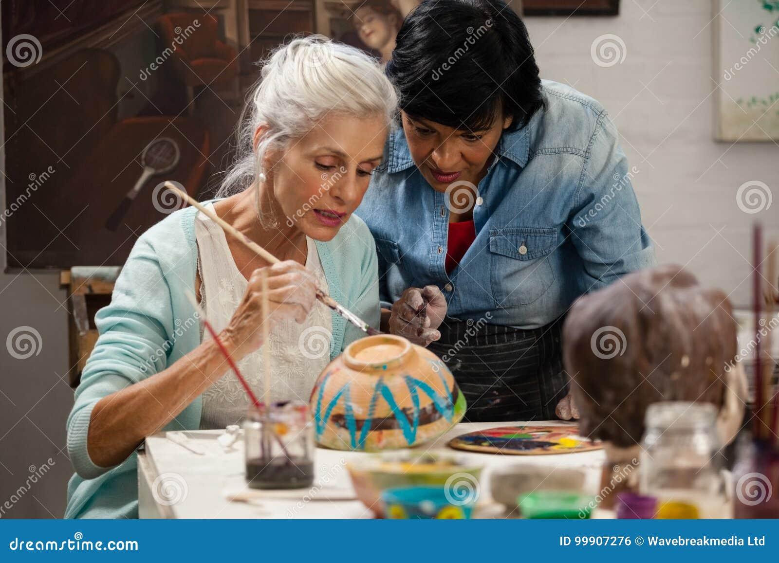 Kobieta pomaga starszej kobiety w obrazu pucharze przy rysunkową klasą