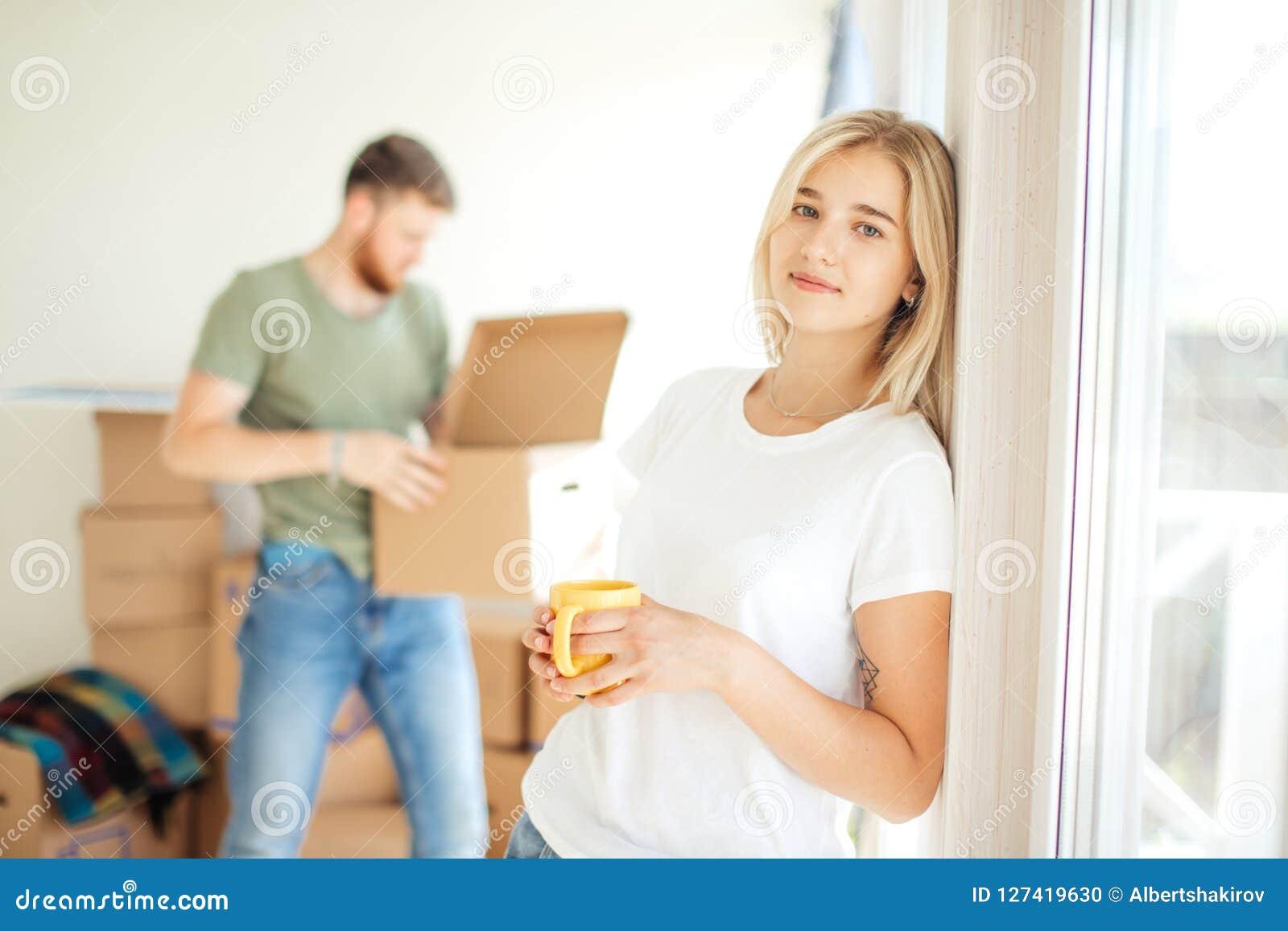 Kobieta pozuje przy kamerą podczas gdy jej mąż lub chłopak odpakowywamy pudełka pary ich domowy poruszający nowy