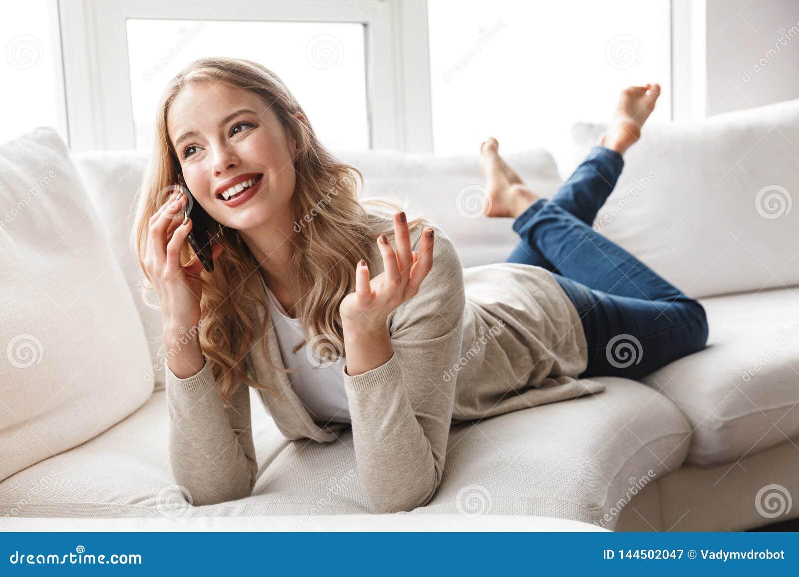 Kobieta pozuje siedz?cy indoors w domu opowiada? telefonem kom?rkowym