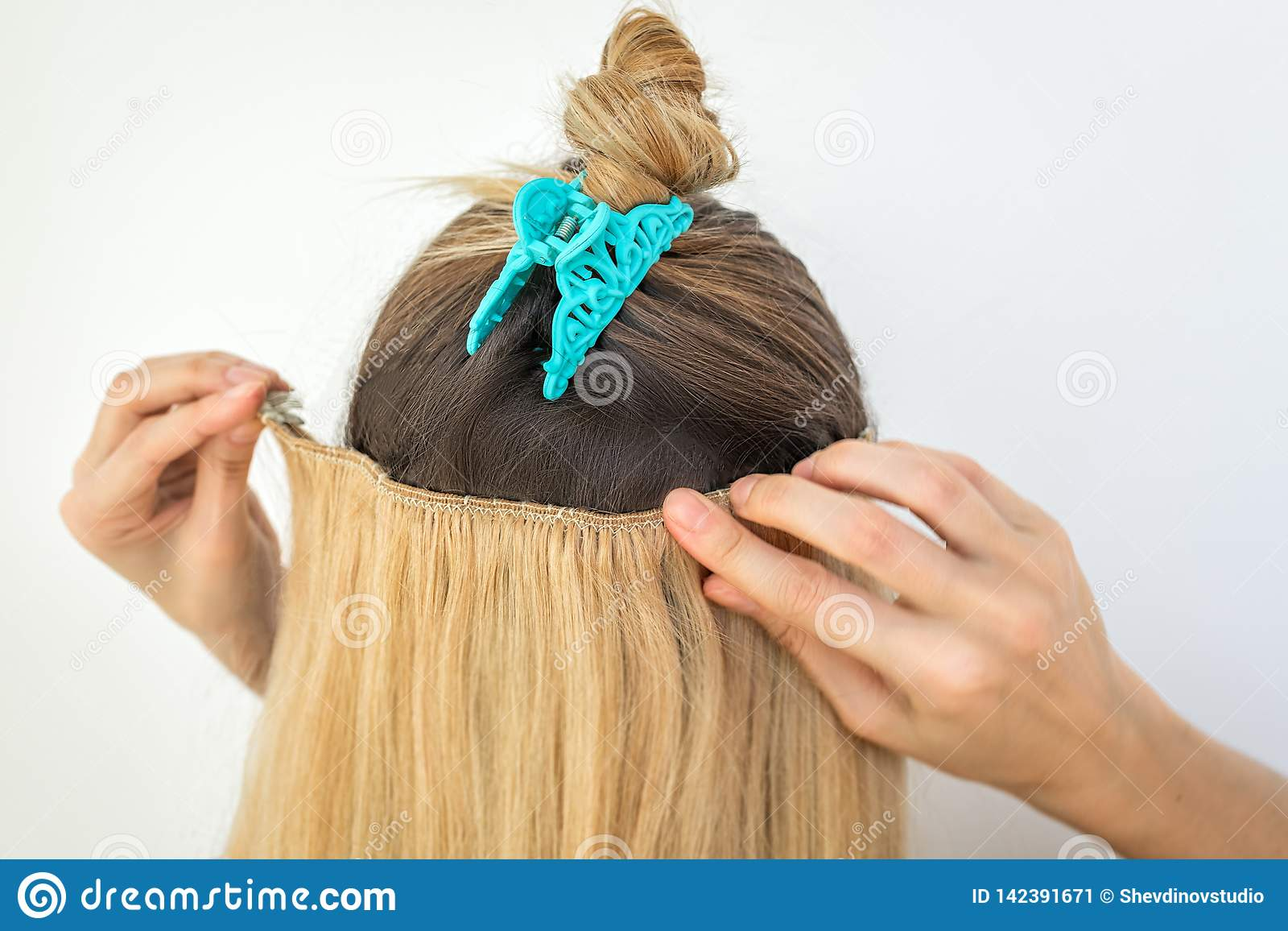 Kobieta próbuje dalej blondynki remy klamerki rozszerzenia naturalne włosiane klamerki