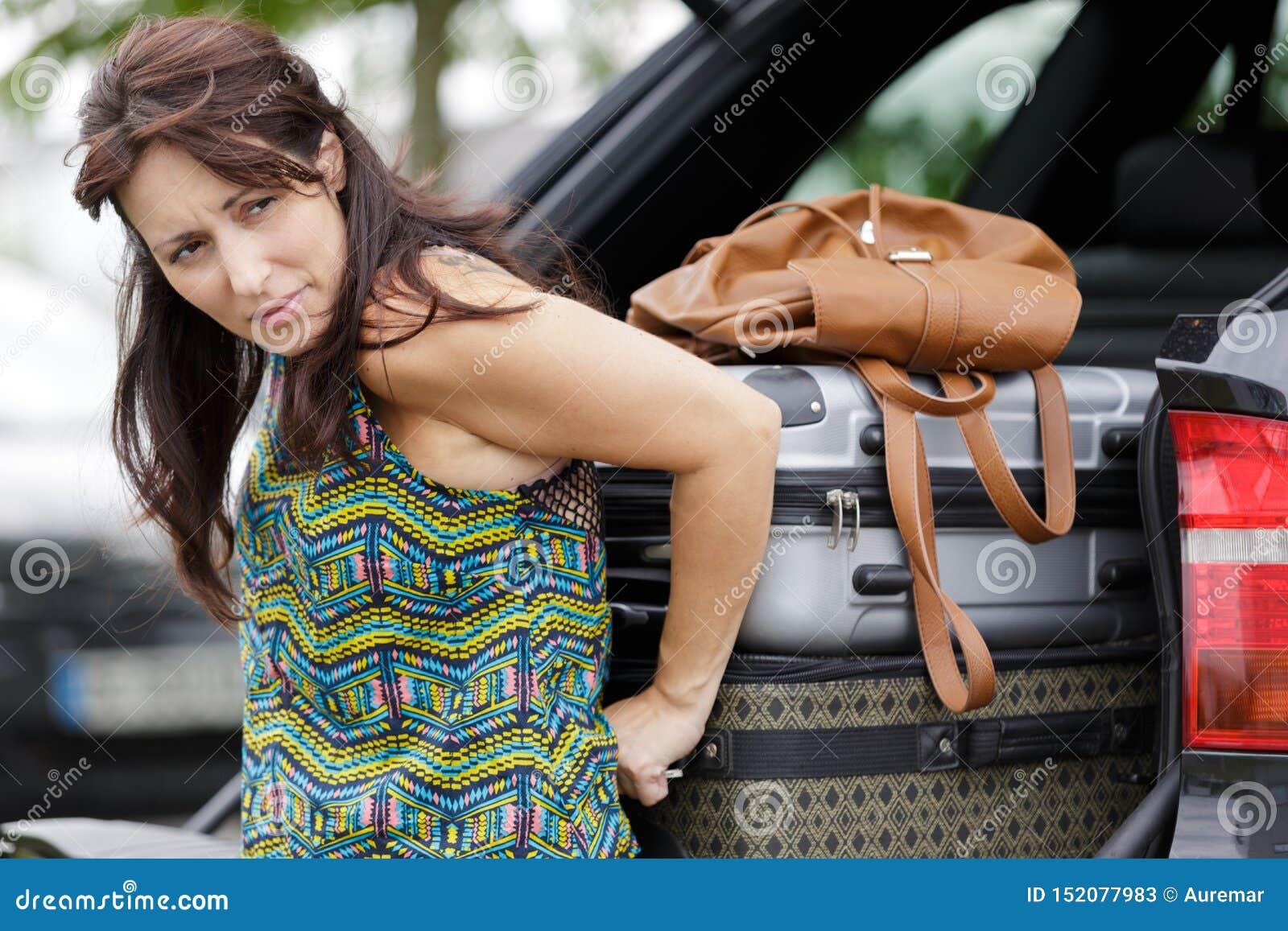 Kobieta próbuje gnieść bagaż w samochodowego but