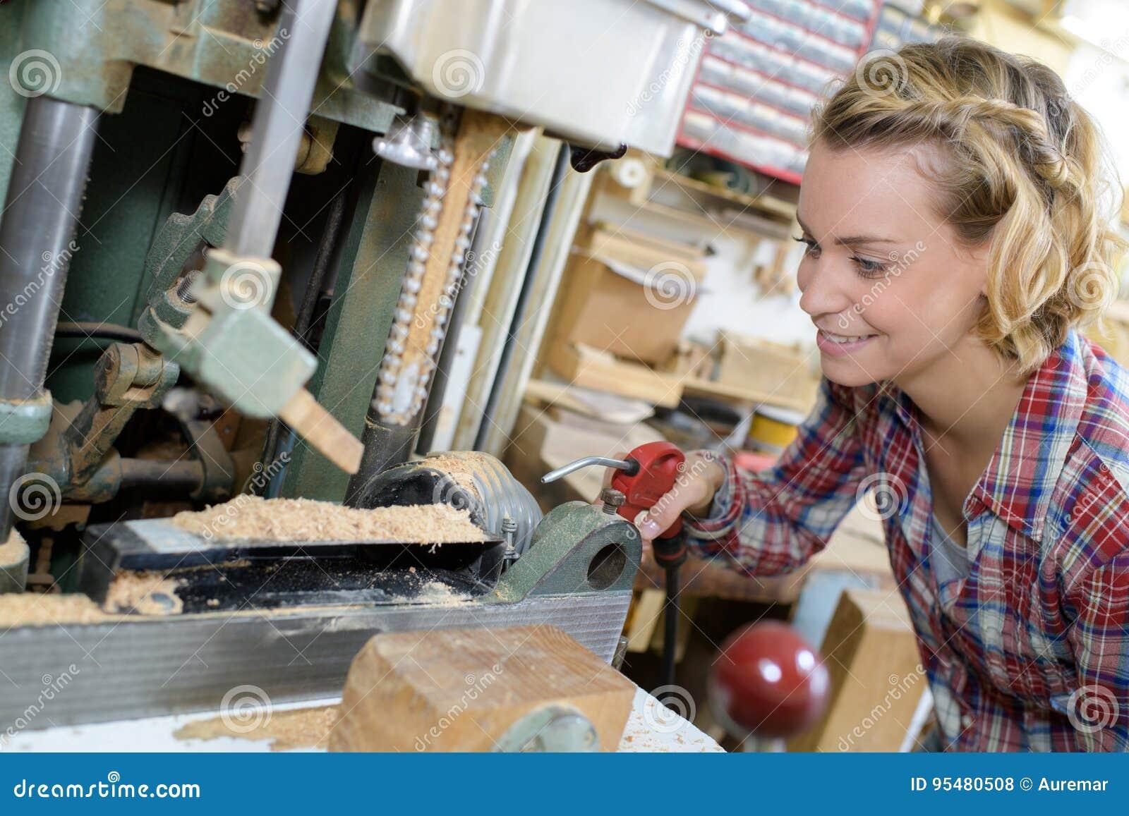 Kobieta pracuje na wiertniczych maszynach w metalworking sklepie