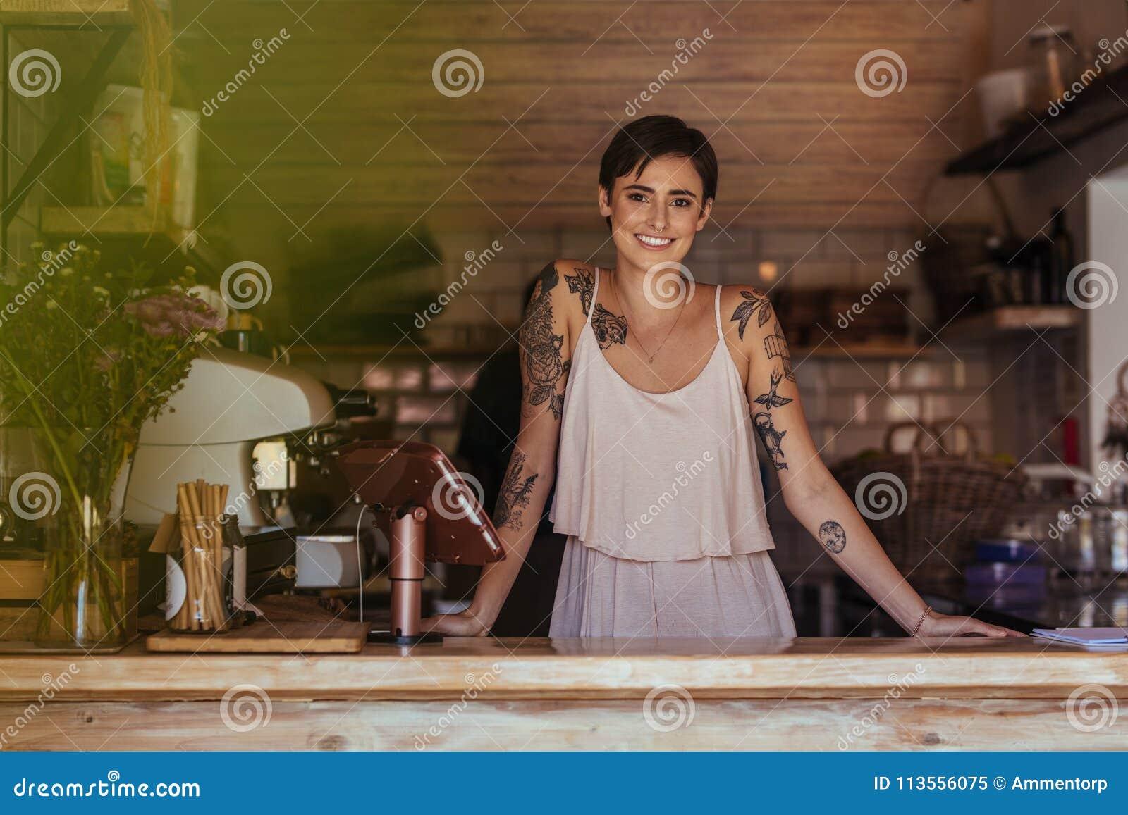 Kobieta przedsiębiorcy pozycja przy kontuarem jej kawiarnia