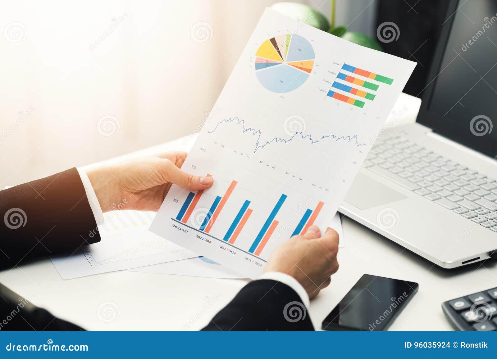 Kobieta przy biurem analizuje biznesowego pieniężnego wykres donosi