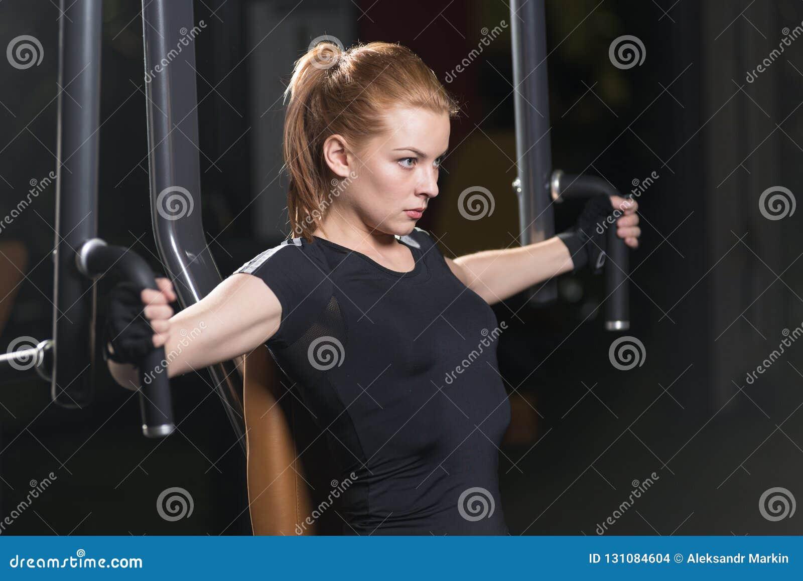Kobieta przy sporta gym robi ręk ćwiczeniom na maszynie