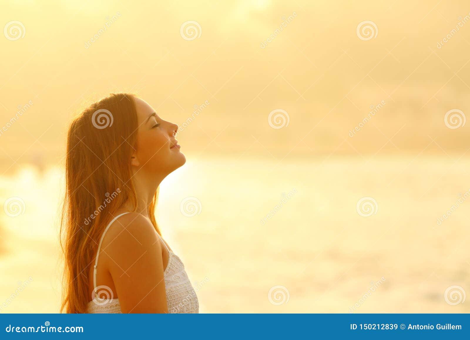 Kobieta przy zmierzchu oddychania relaksującym świeżym powietrzem