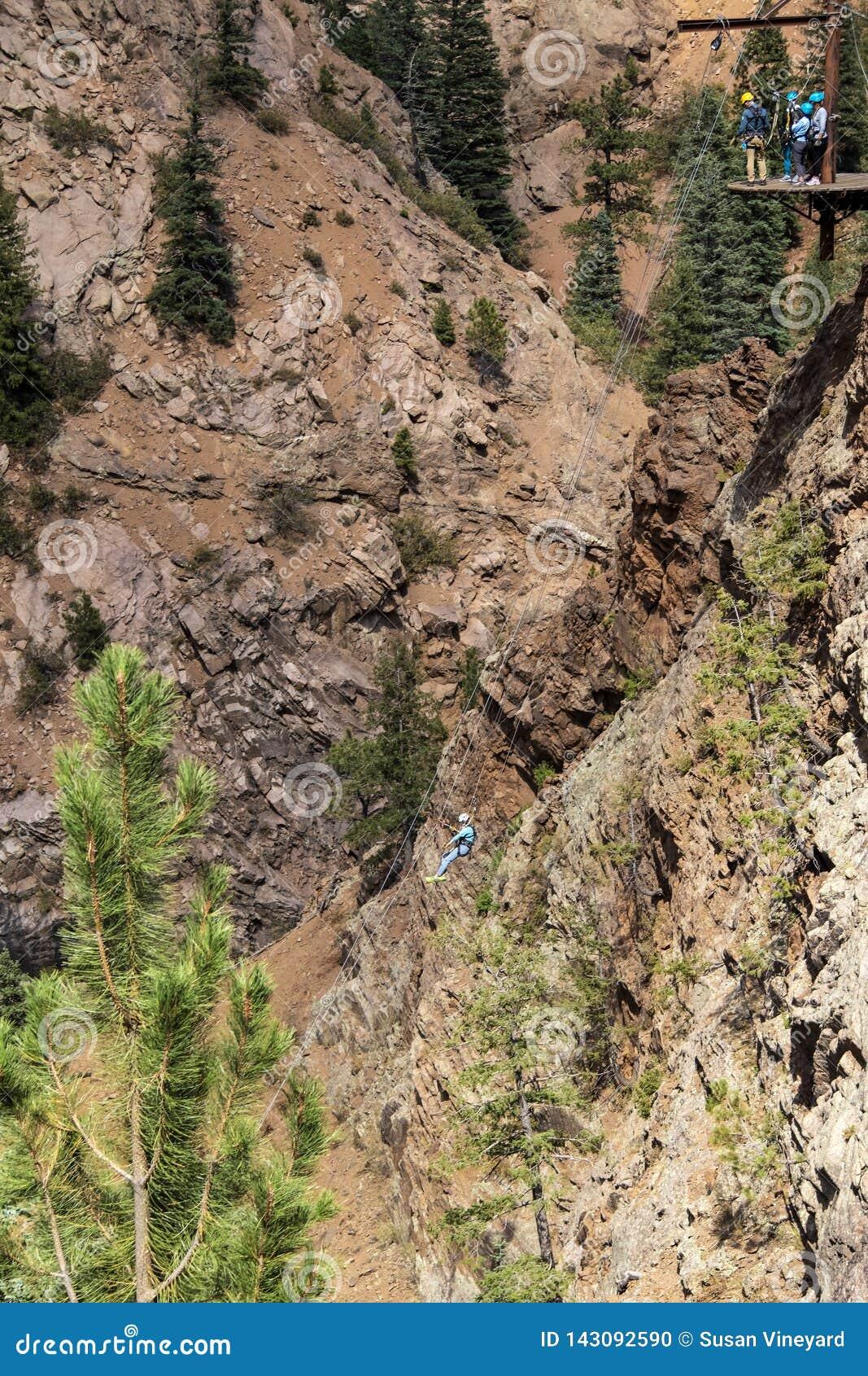 Kobieta rappelling w dół stroma i wysoka halna faleza w Skalistych górach z grupa ludzi czekaniem na platformie dla ich zwrota