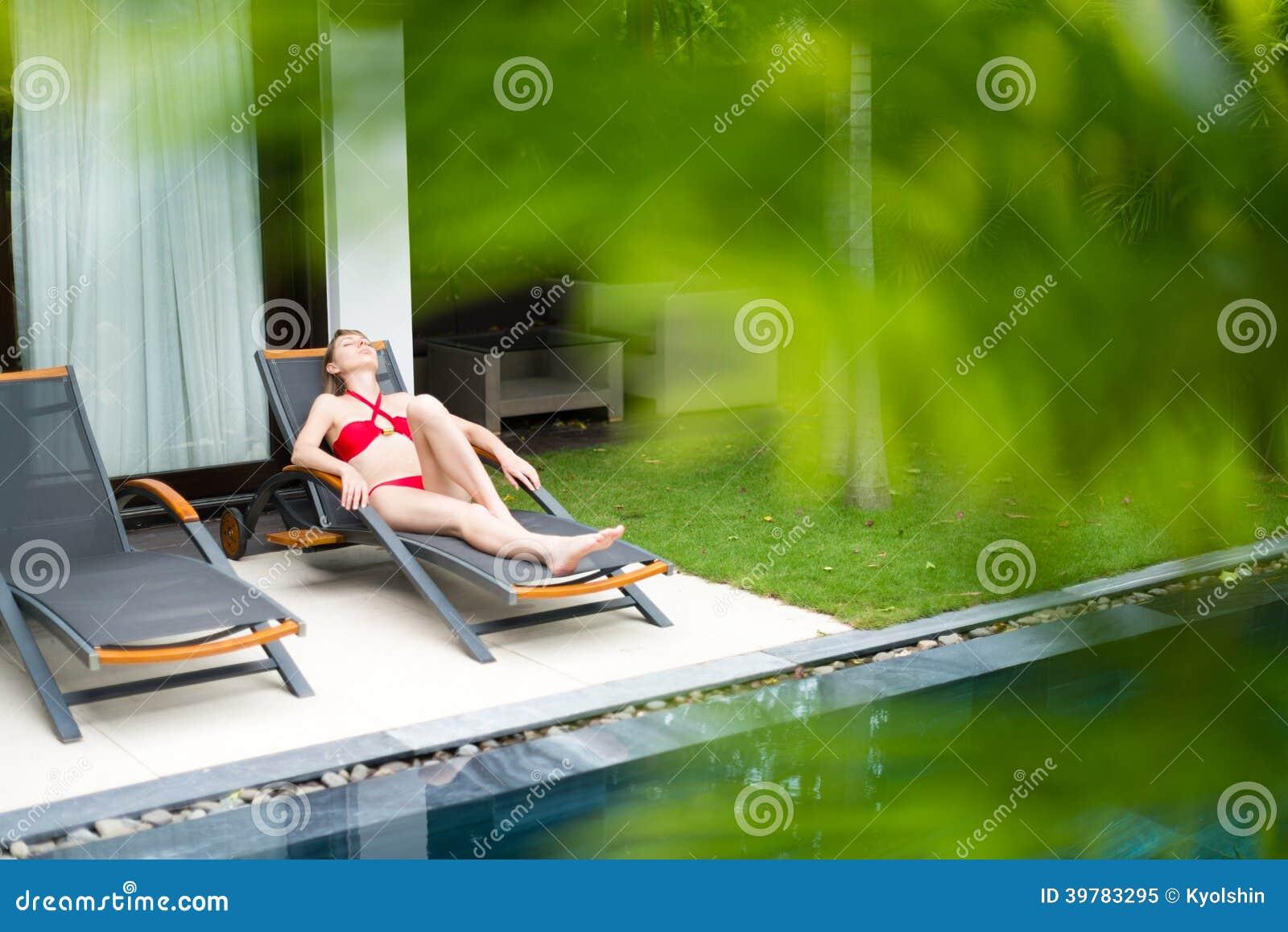 Kobieta relaksuje na bryczki longue pobliskim basenie.