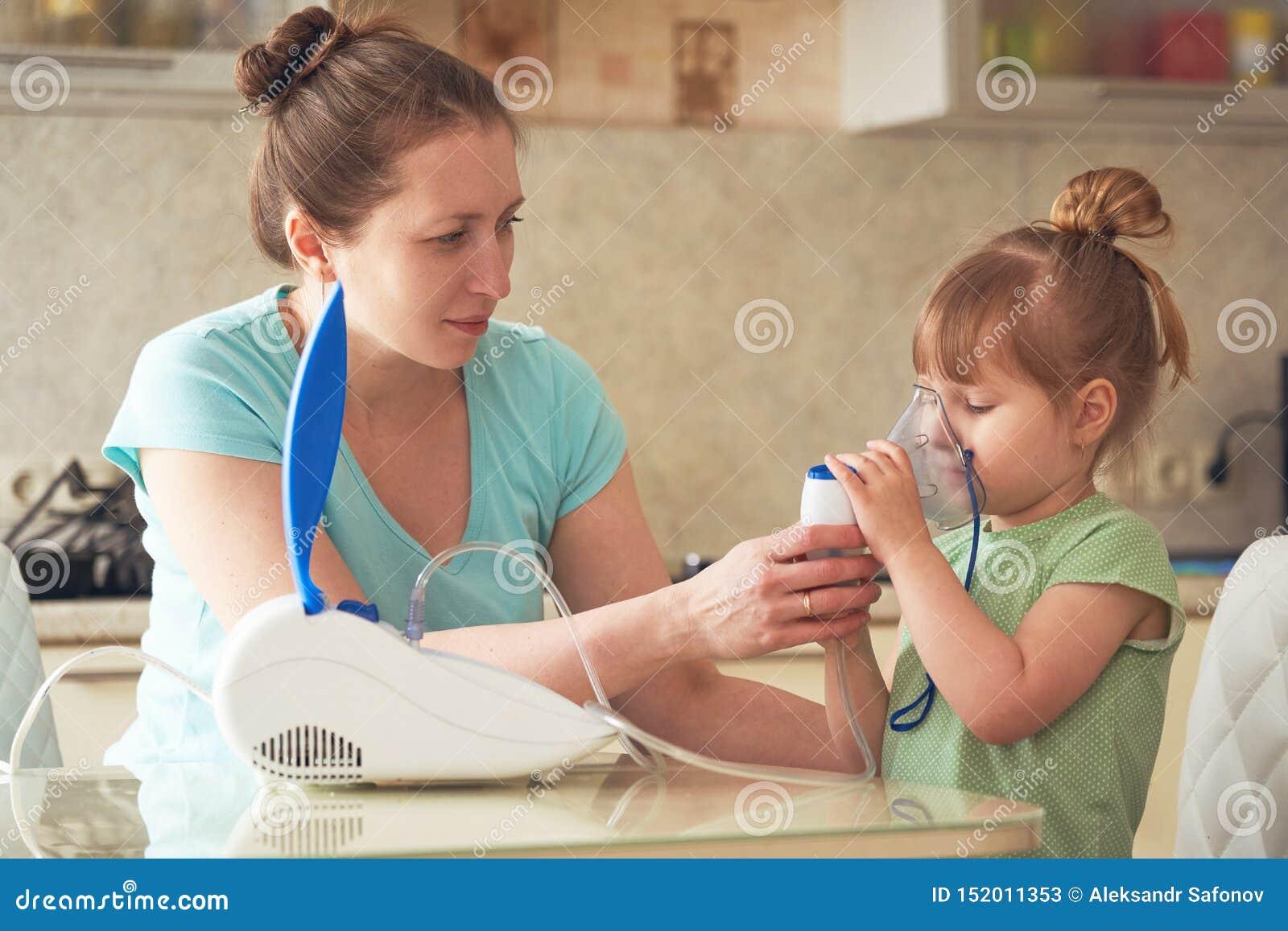Kobieta robi inhalacji dziecko w domu przynosi nebulizer maskę jego twarz wdycha opary lekarstwo dziewczyna 2th lat confusedly