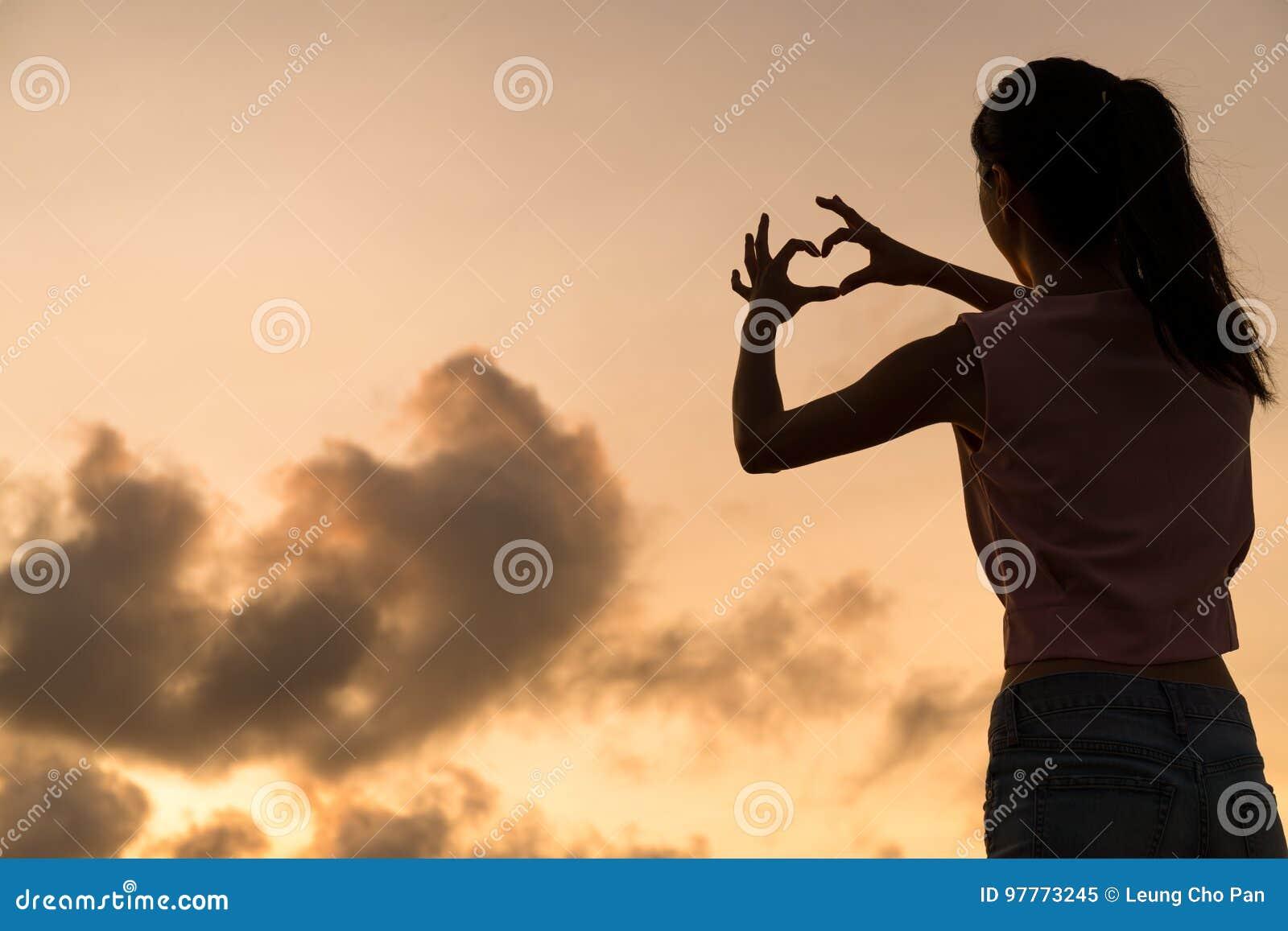 Kobieta robi kierowemu symbolowi z jej rękami przy zmierzchem
