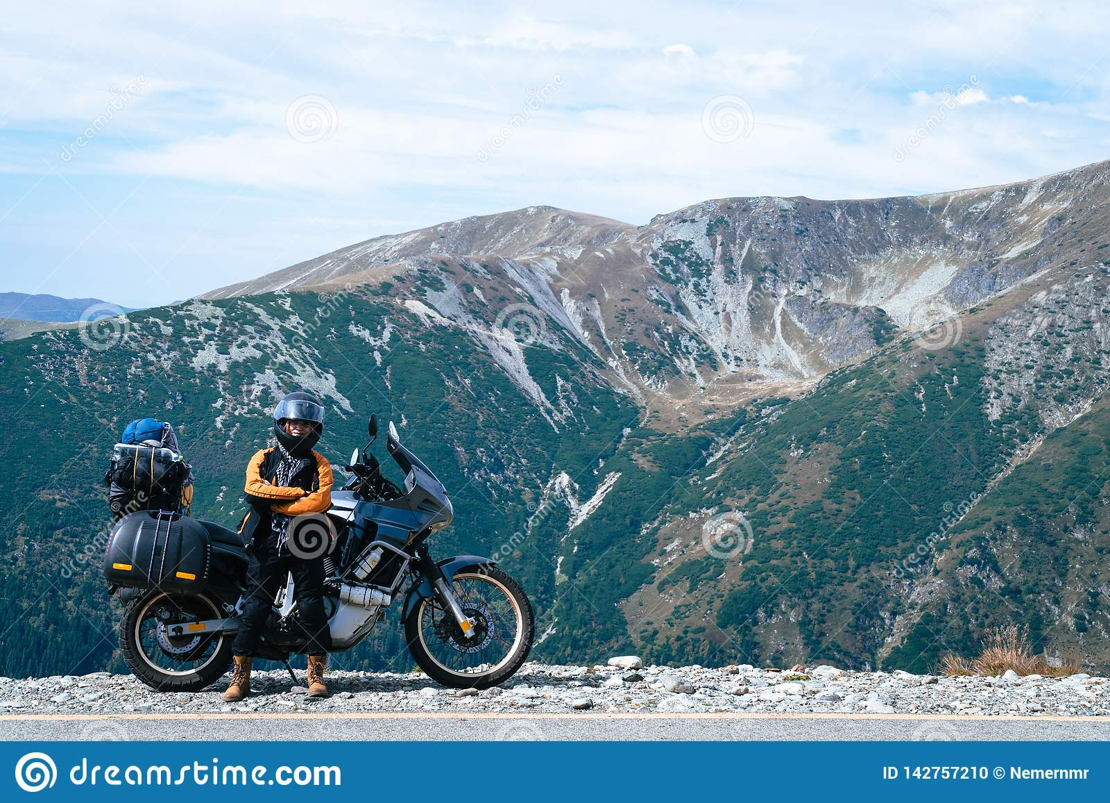 Kobieta rowerzysta i adveture motocykl nakrywamy halną drogę Podróżuje, wakacje w Europa, motocyklisty sposób, turystyka, Transal