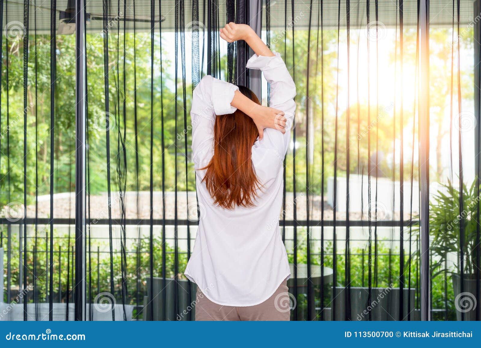 Kobieta rozciąga ona ręki podczas gdy trwanie i przyglądający wschód słońca thr
