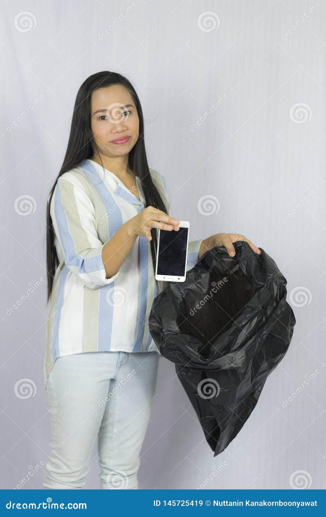 Kobieta rzuca jej telefon w torb? na ?miecie, pozowa? odizolowywam na szarym tle