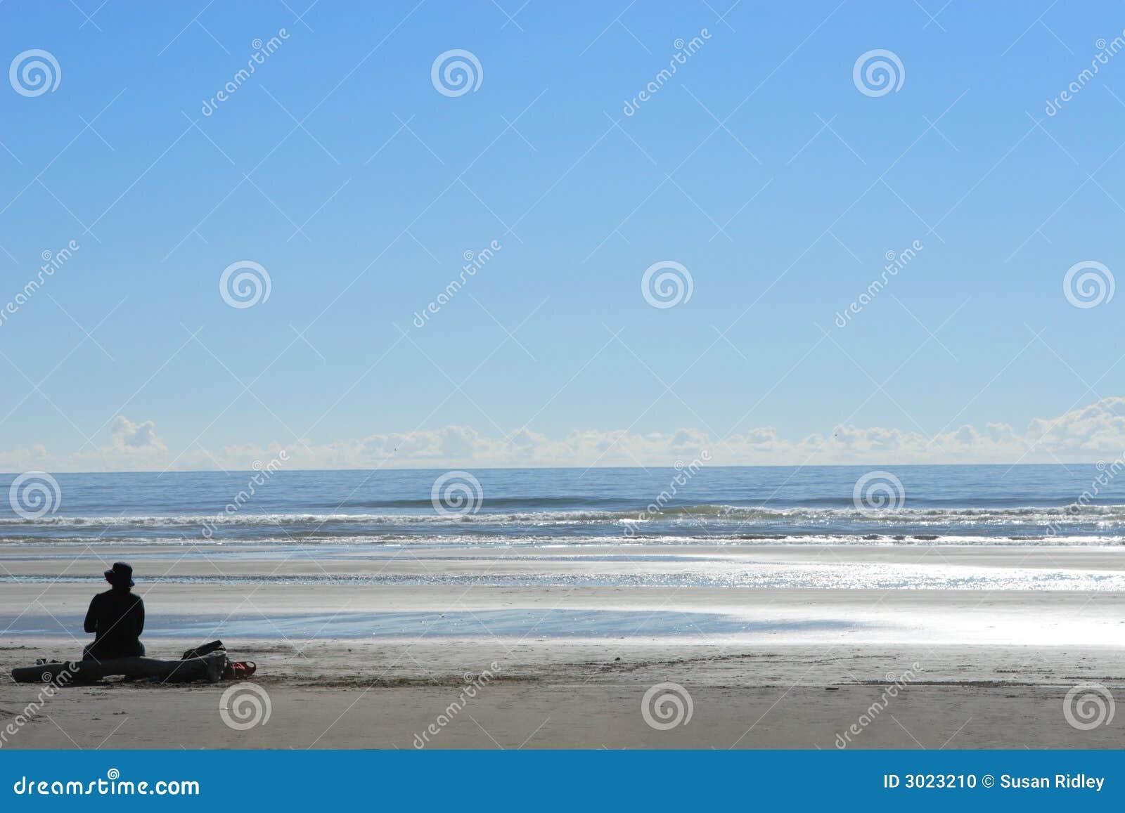 Kobieta siedząca samotnie plażowa