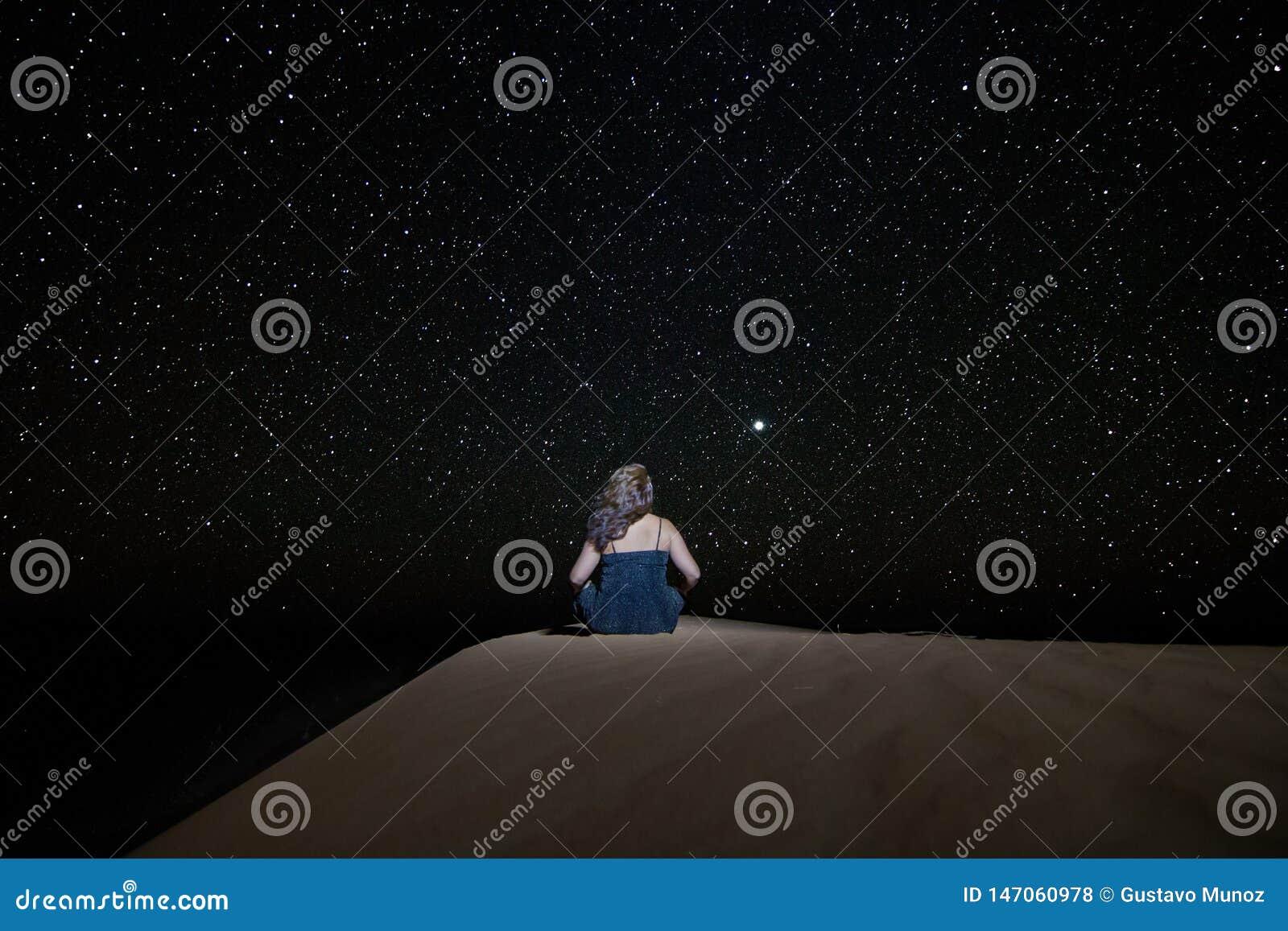 Kobieta siedzi gapić się przy gwiaździstym niebem w kierunku Wenus, na diunie w erga Chebbi pustyni