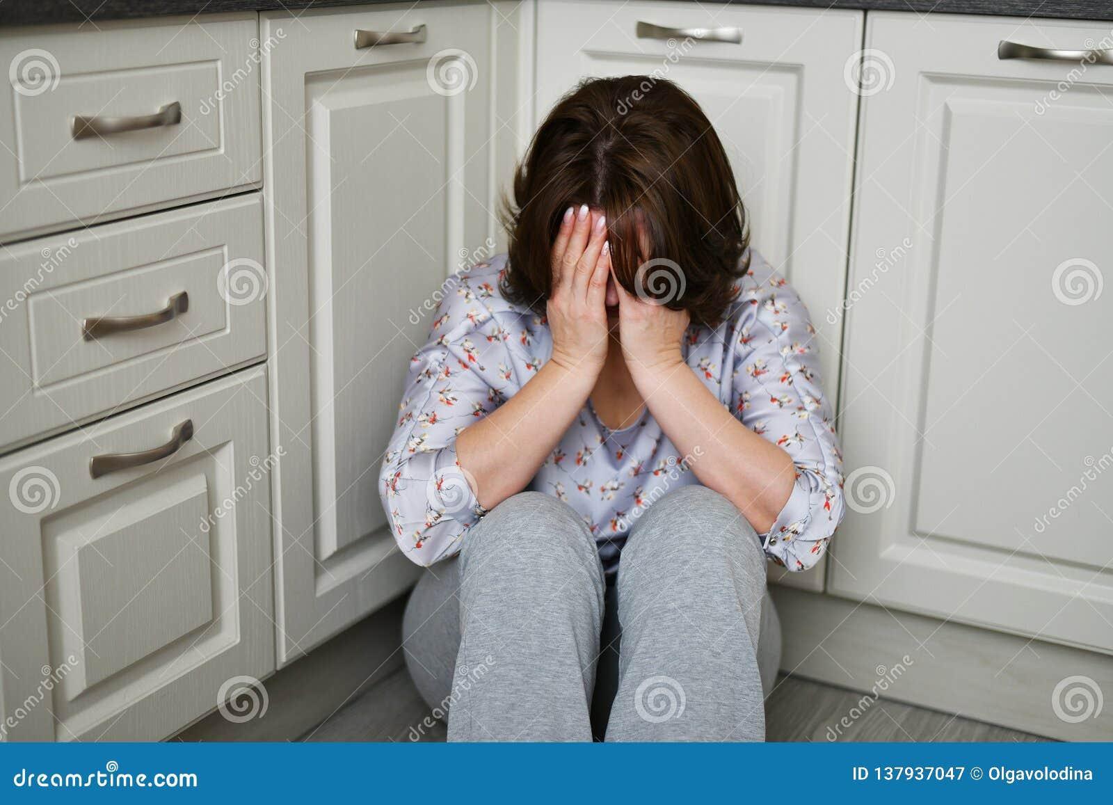 Kobieta siedzi na kuchennym podłogowym nakryciu jej twarz z ona ręki Depresja, żal lub frustracja,