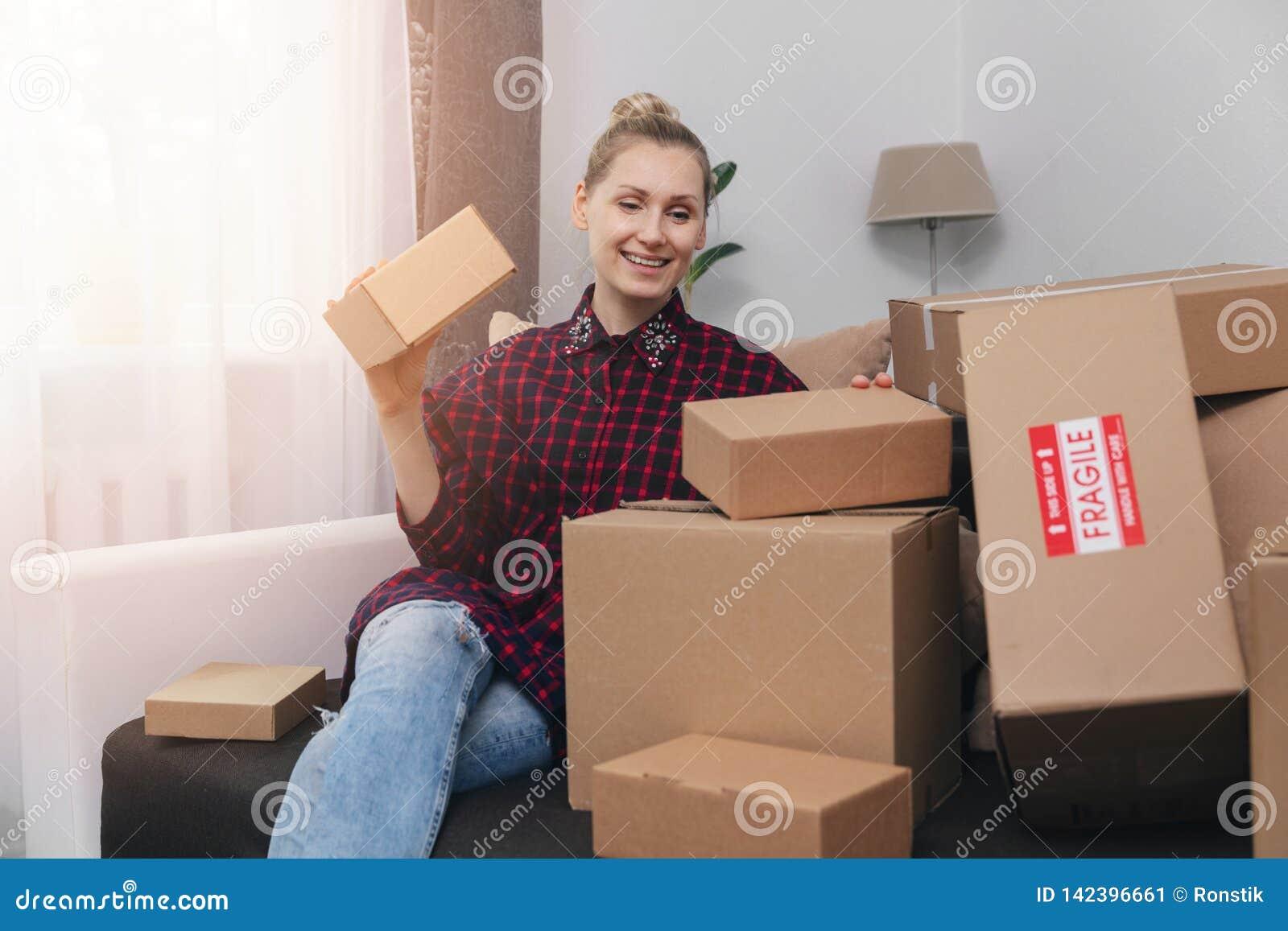 Kobieta siedzi na leżance z udziałem kartony w domu