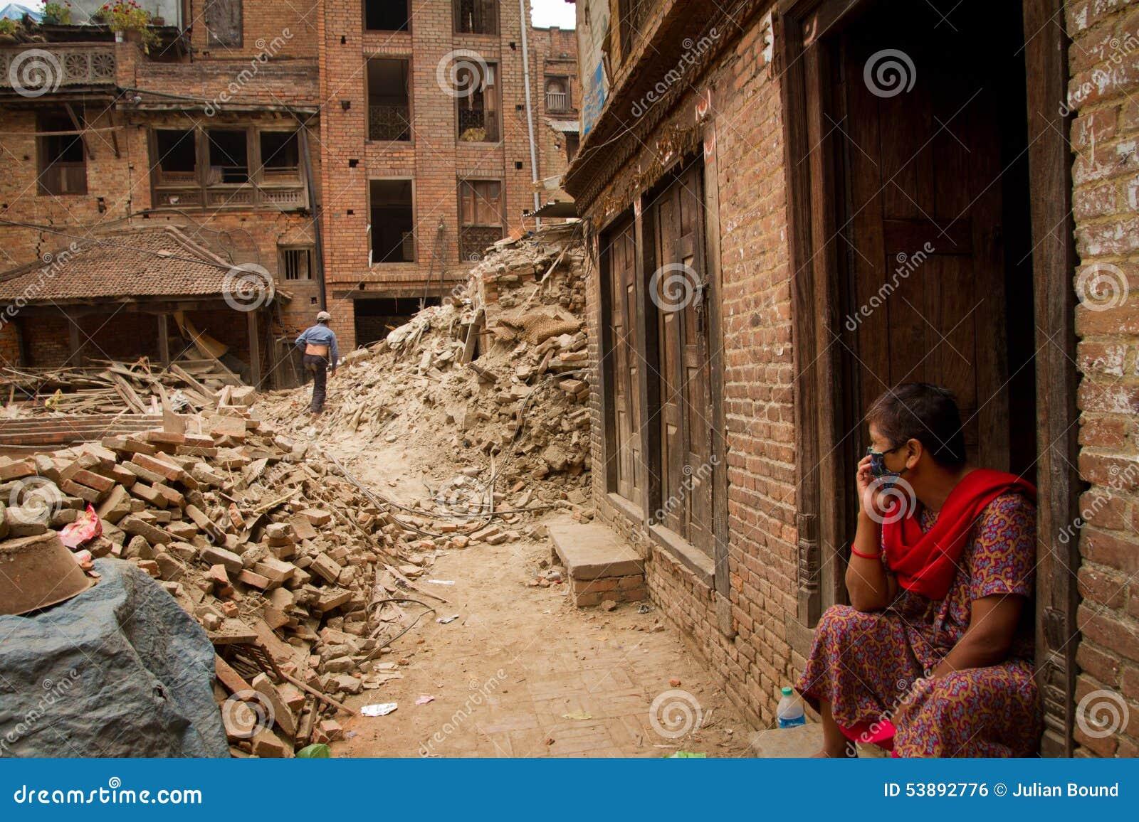Kobieta siedzi na zewnątrz jej trzęsienie ziemi rujnującego domu w Bhaktapu teraz